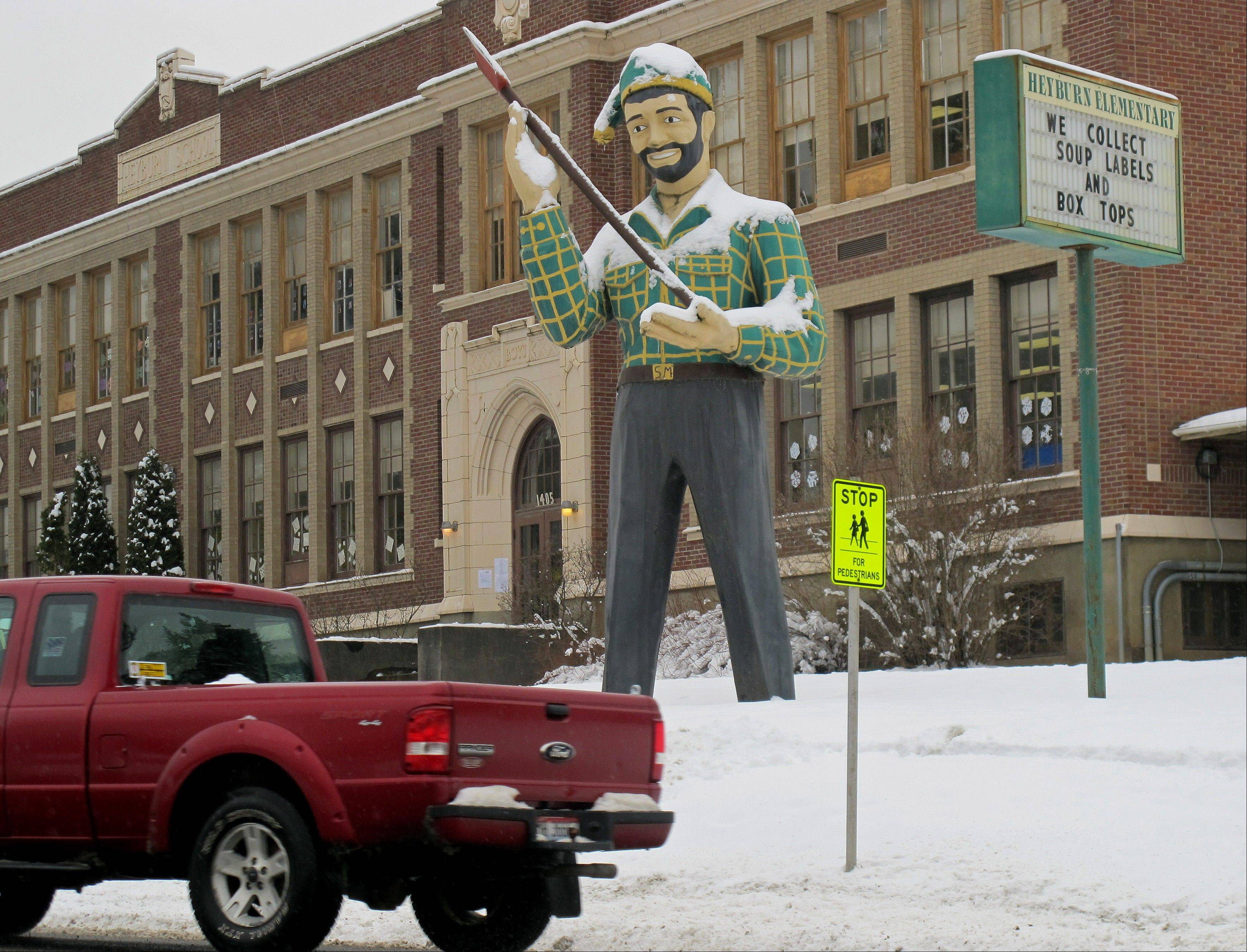 A statue of a logger stands outside an elementary school in St. Maries, Idaho, near where a survivalist group plans to build a compound. The proposal is called the Citadel and has created a buzz among folks in this remote logging town 70 miles southeast of Spokane, Wash.