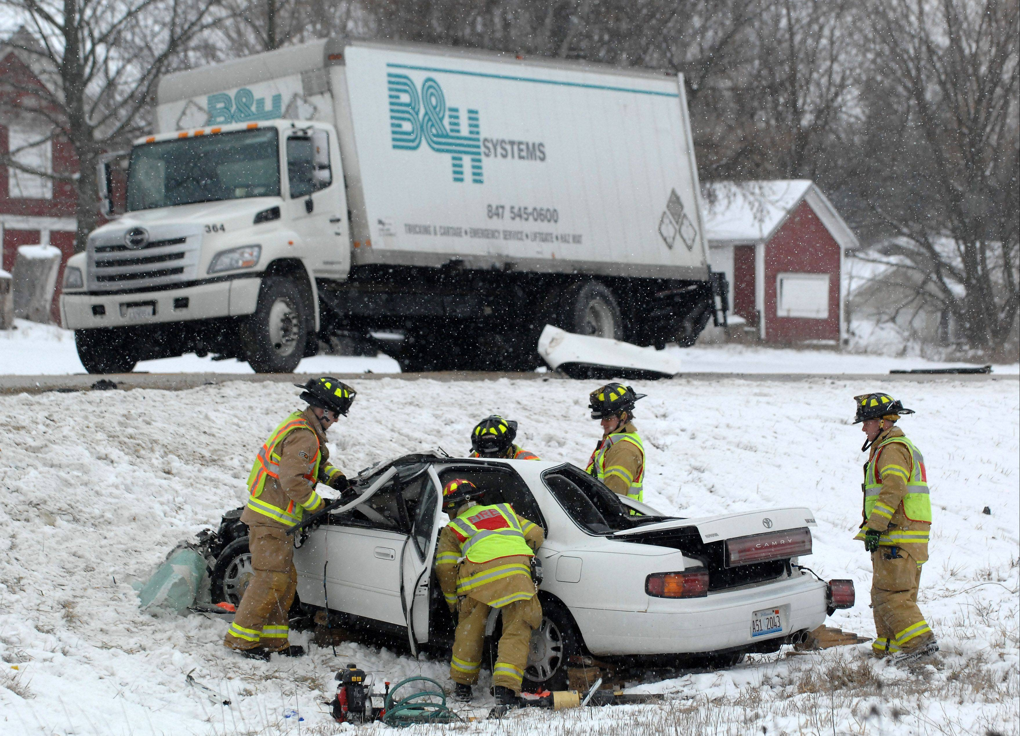 Firefighters work to remove the body of a Kaneville woman who was killed Tuesday morning ina two-vehicle accident involving a truck on Route 38 near Francis Road in Elburn.