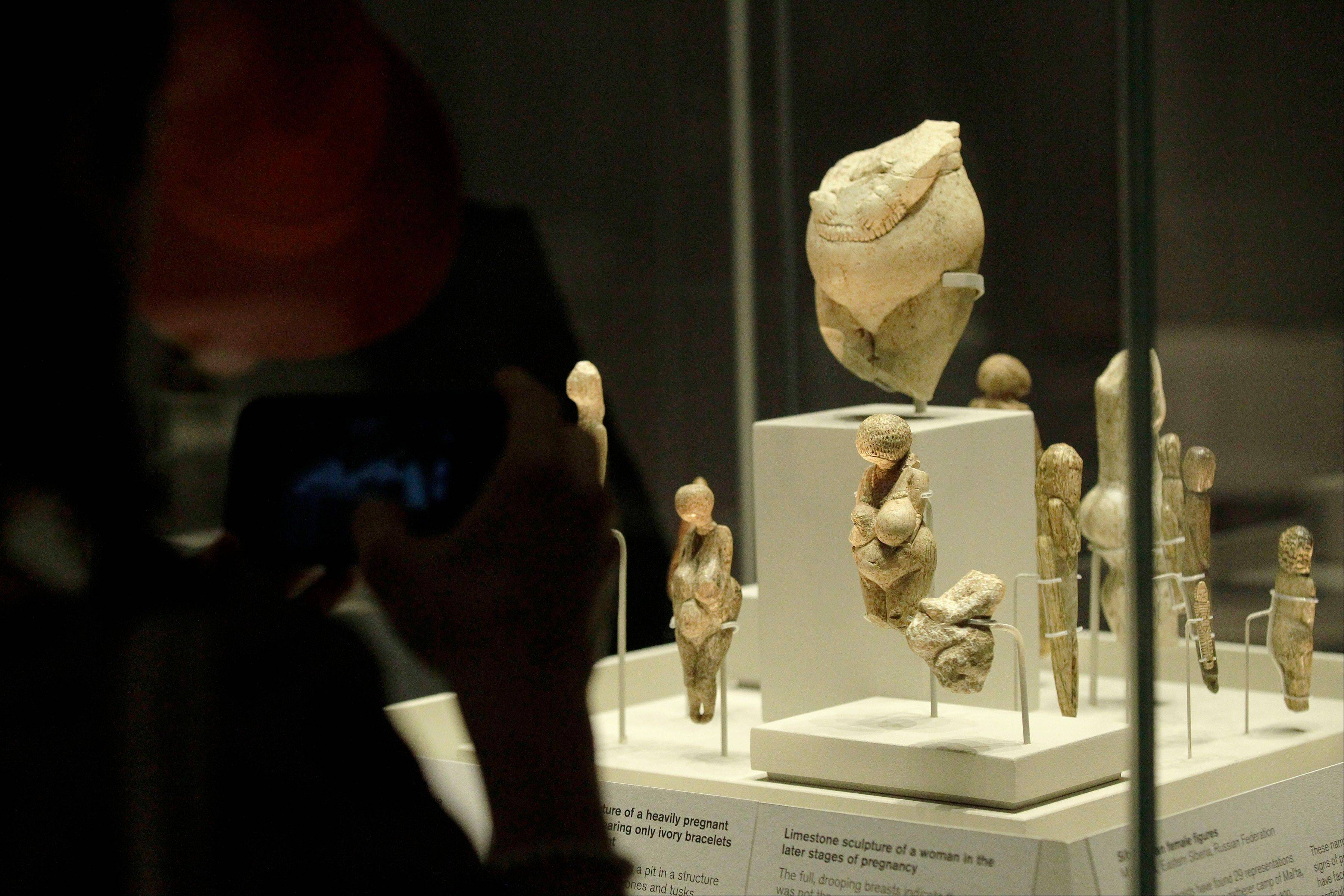 Visitors look at sculptures of pregnant women on display in an exhibition 'Ice Age Art : arrival of the modern mind' at the British Museum in London.