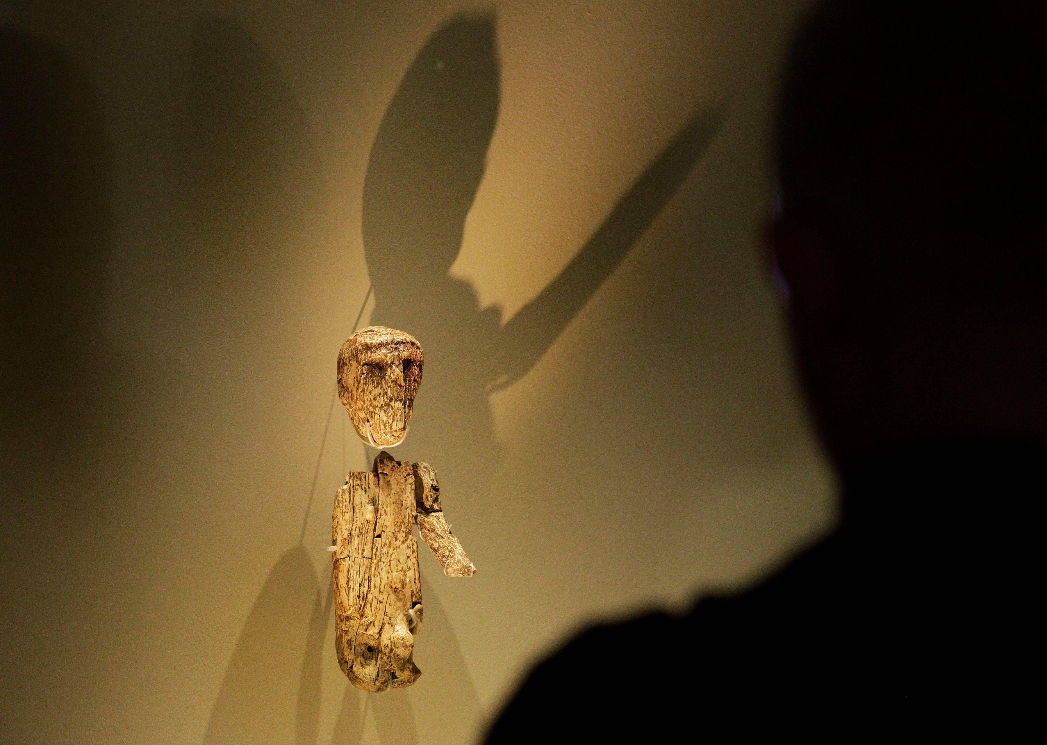 A visitor looks at a small male figure sculptured from a large mammoth tusk that dates around 27,000 years ago, discovered at Brno, Moravia, Czech Republic next to a skeleton of a man.