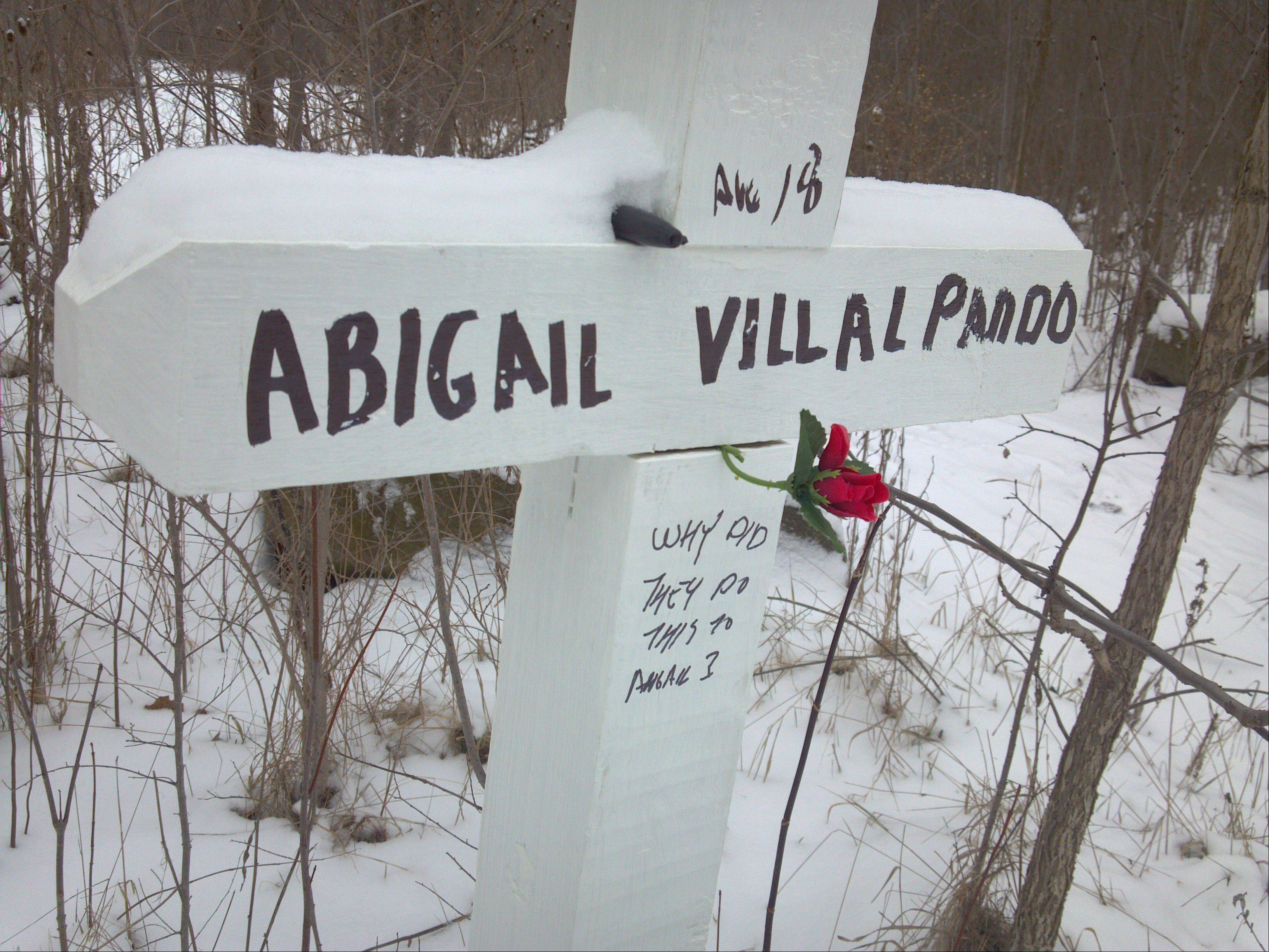 A white cross in memory of Abigail Villalpando was placed near Fifth Street and Wabansia Avenue in Montgomery, near where her burned remains were found by sheriff's deputies. Three men have been charged in connection with her murder, which was the first homicide in Aurora since late 2011.