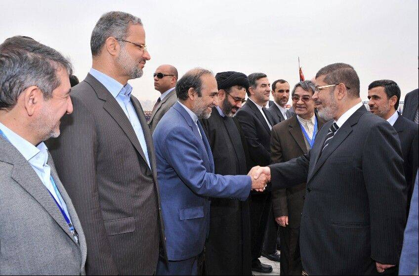 Associated PressIran's President Mahmoud Ahmadinejad, right, looks on as and Egyptian President Mohammed Morsi, second right, shakes hands with the Iranian delegation at the airport in Cairo, Egypt, Tuesday, Feb. 5, 2013. Ahmadinejad arrived in Cairo on Tuesday for the first visit by an Iranian leader in more than three decades, marking a historic departure from years of frigid ties between the two regional heavyweights.
