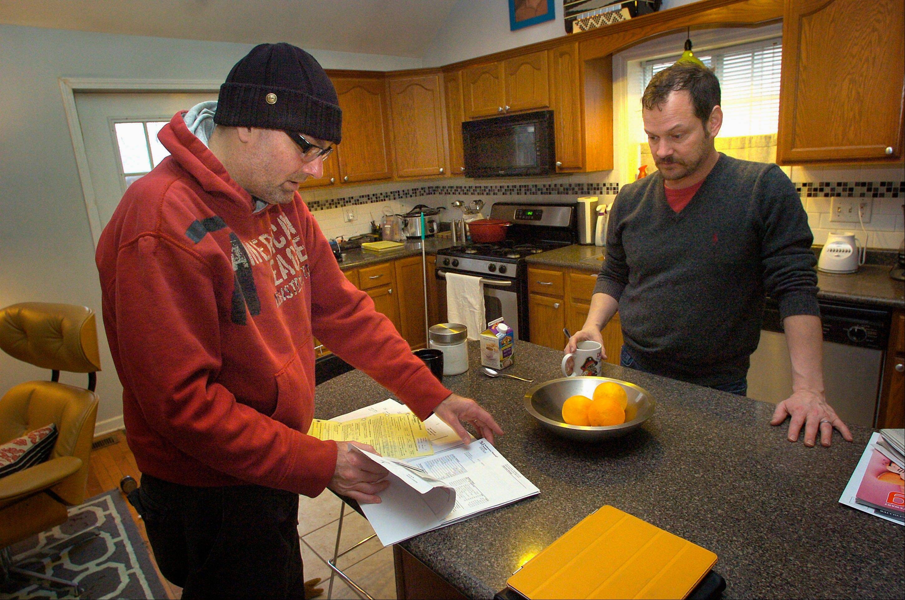 Noah Dean Baker, left, and his partner, Ken Sprouls, look over the bill Baker received for a liver transplant at their home in Bloomington.
