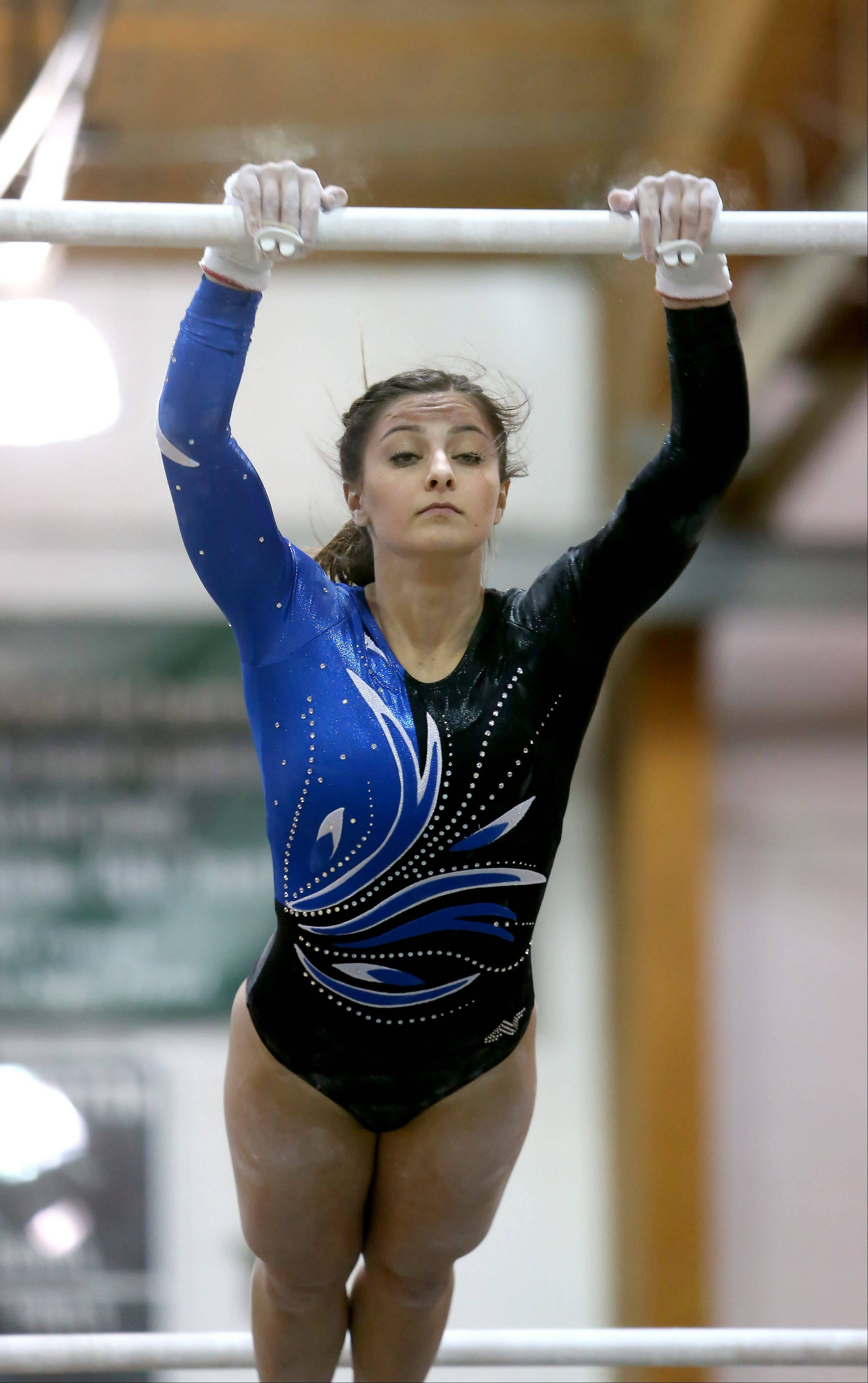 Dominique Brognia of Geneva performs on the uneven parallel bars during sectional gymnastics at Glenbard West on Tuesday in Glen Ellyn.