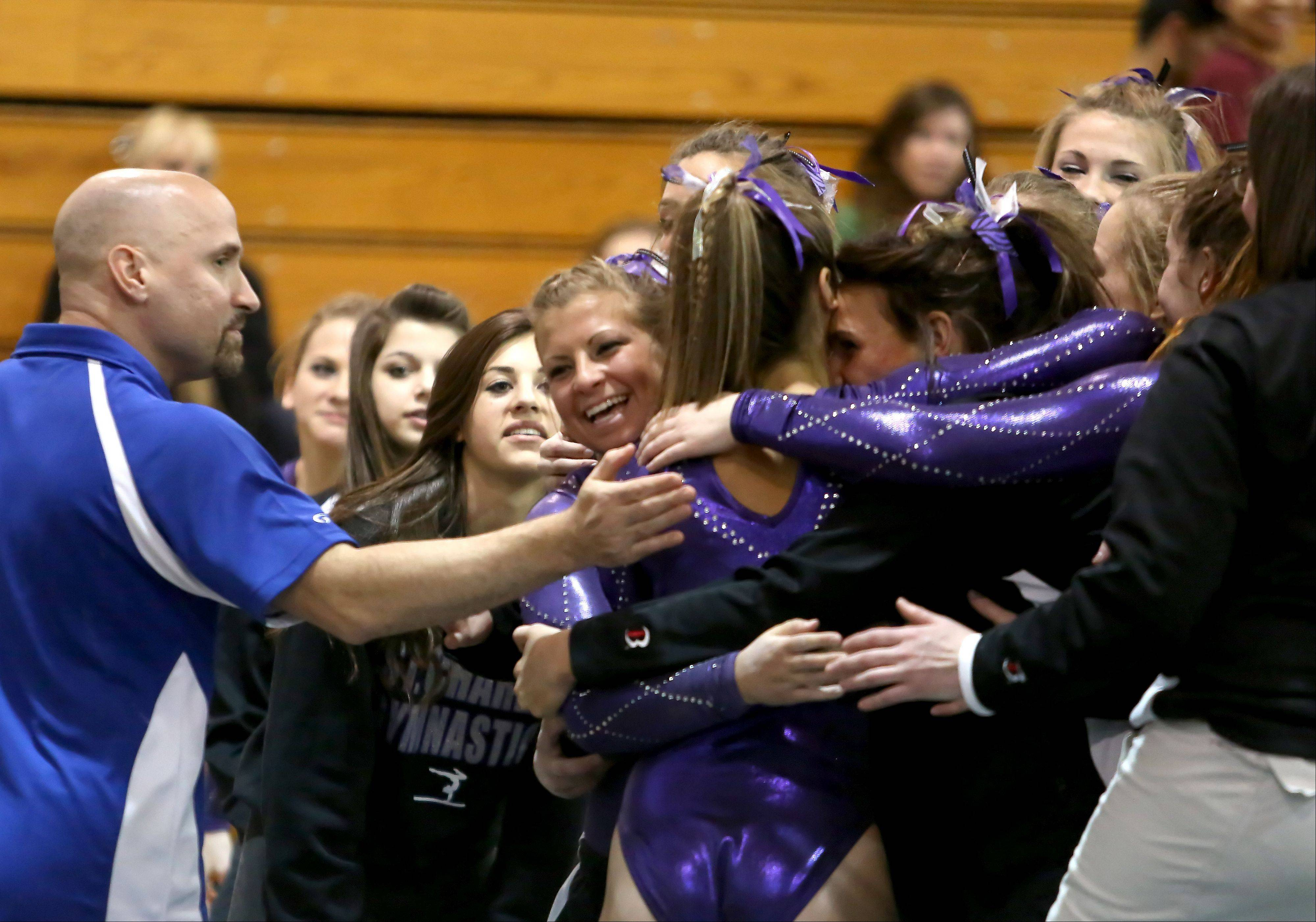 Sam Upshaw of St. Charles co-op, is congratulated by her teammates after her beam routine at the sectional gymnastics championship at Glenbard West on Tuesday in Glen Ellyn.