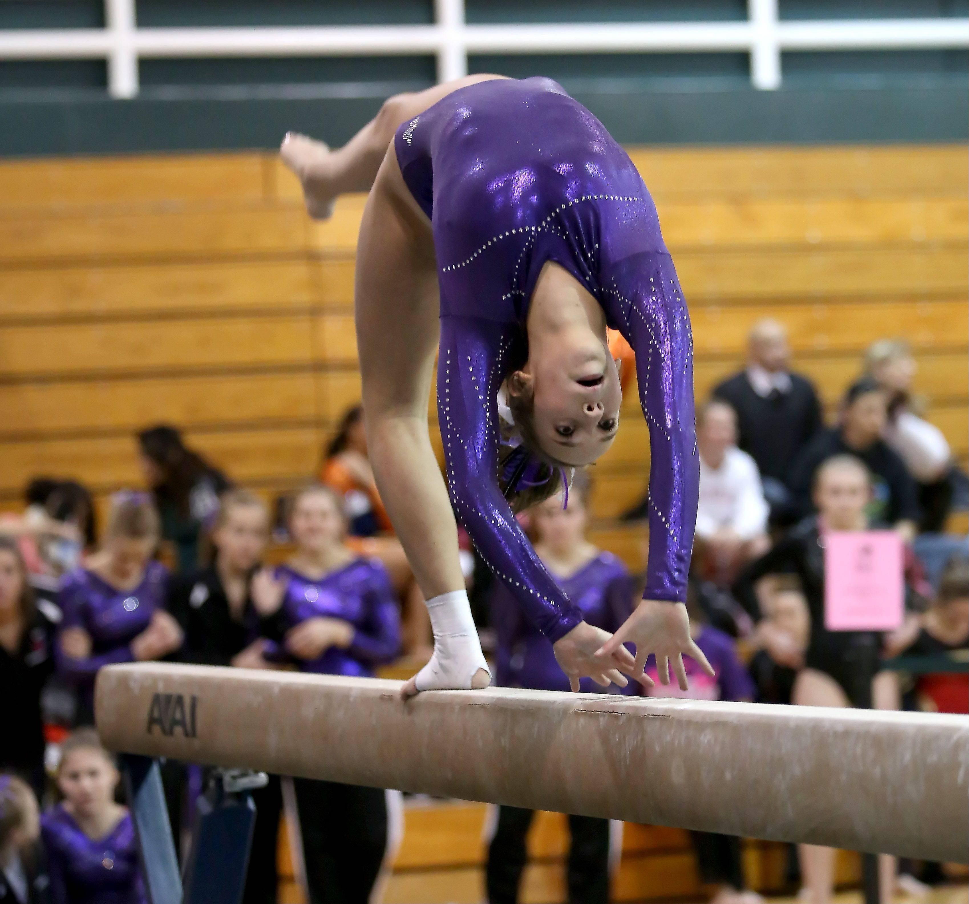 Sam Upshaw of St. Charles co-op, performs her beam routine at the sectional gymnastics championship at Glenbard West on Tuesday in Glen Ellyn.
