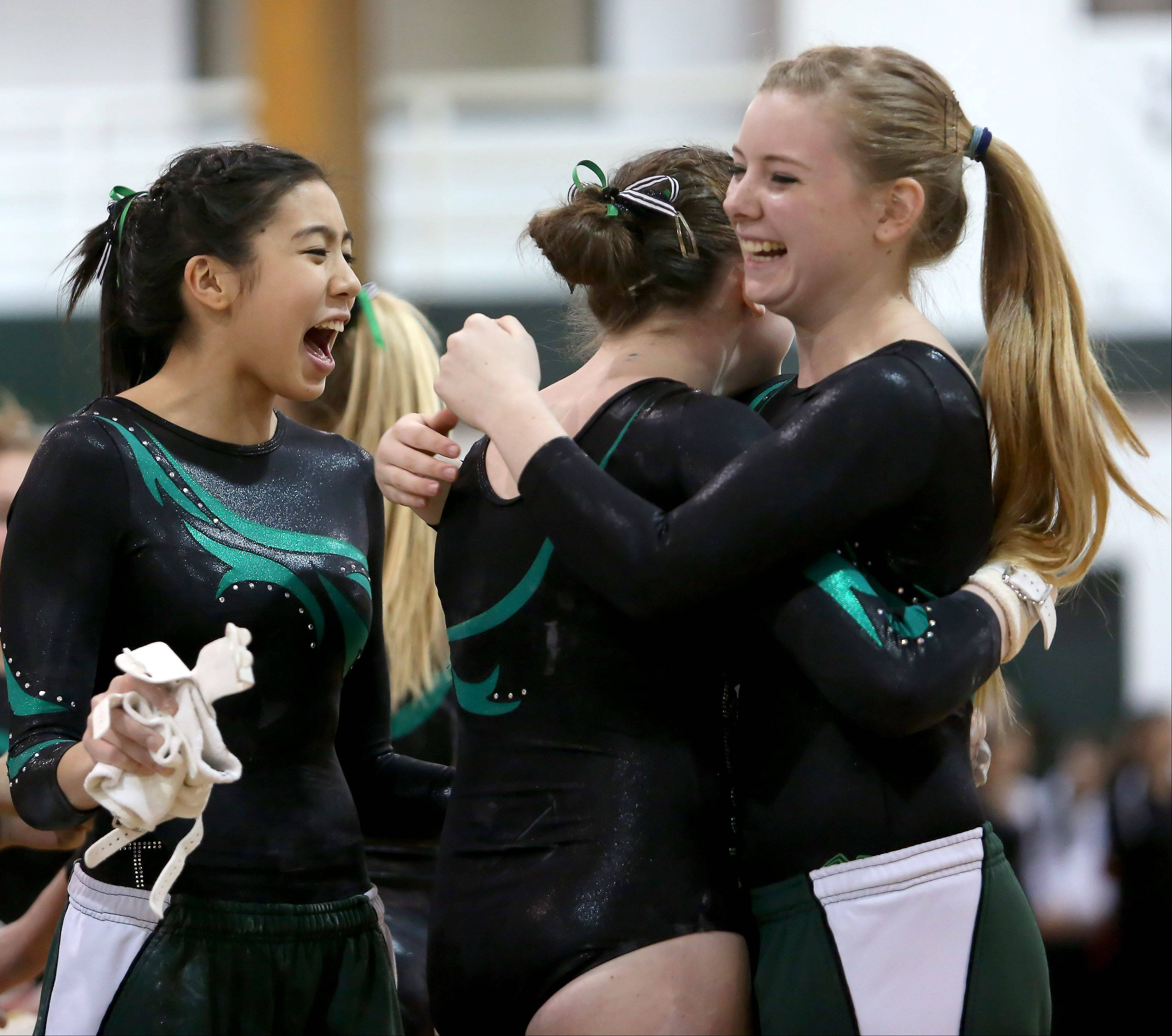 Mackenzie O'Keefe, center, of Glenbard West is congratulated by teammates after her uneven parallel bars routine at sectional gymnastics at Glenbard West on Tuesday in Glen Ellyn.