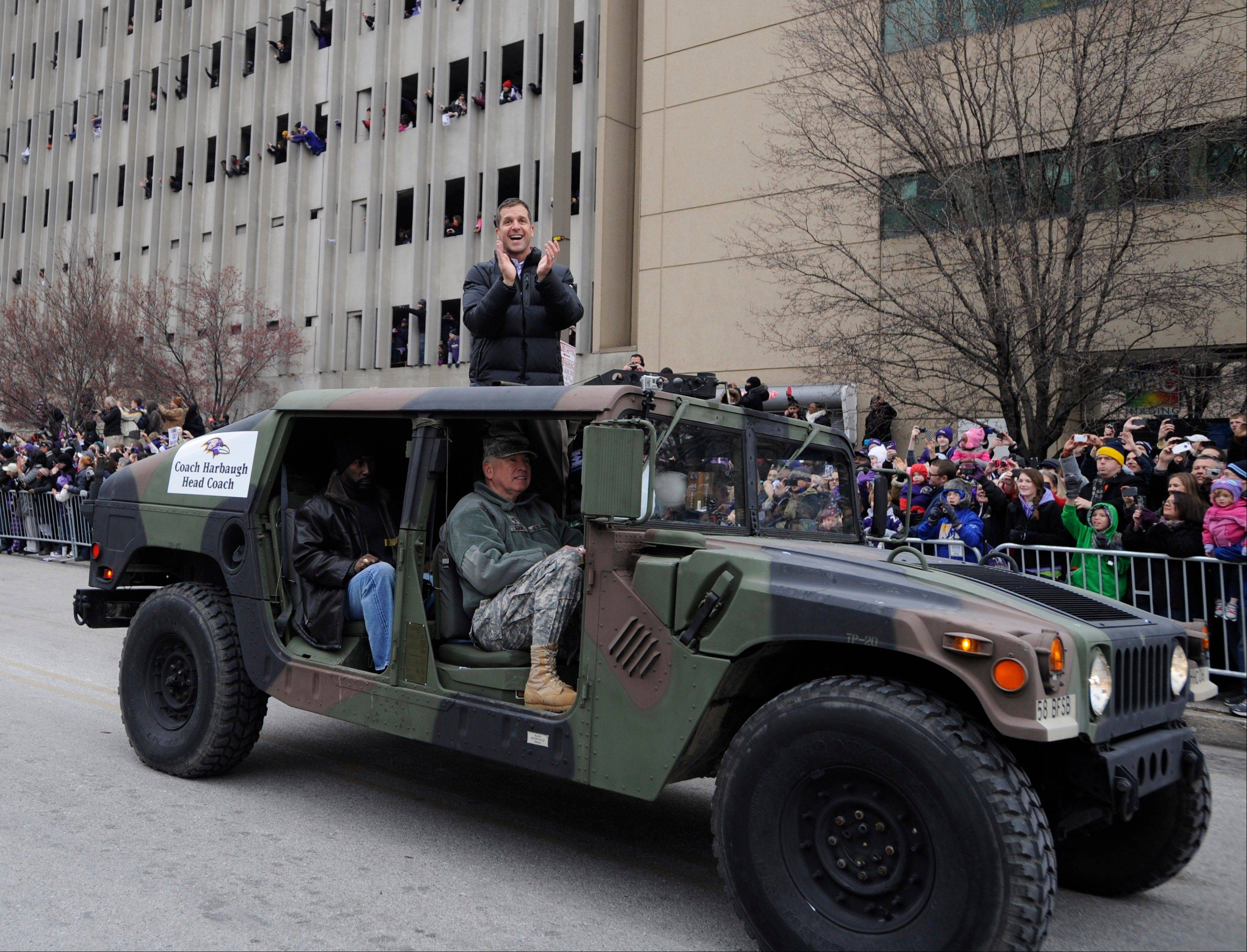 Baltimore Ravens head coach John Harbaugh applauds fans while riding in a Humvee during the Ravens victory parade Tuesday, Feb. 5, 2013, in Baltimore. The Ravens defeated the San Francisco 49ers in NFL football's Super Bowl XLVII 34-31 on Sunday.