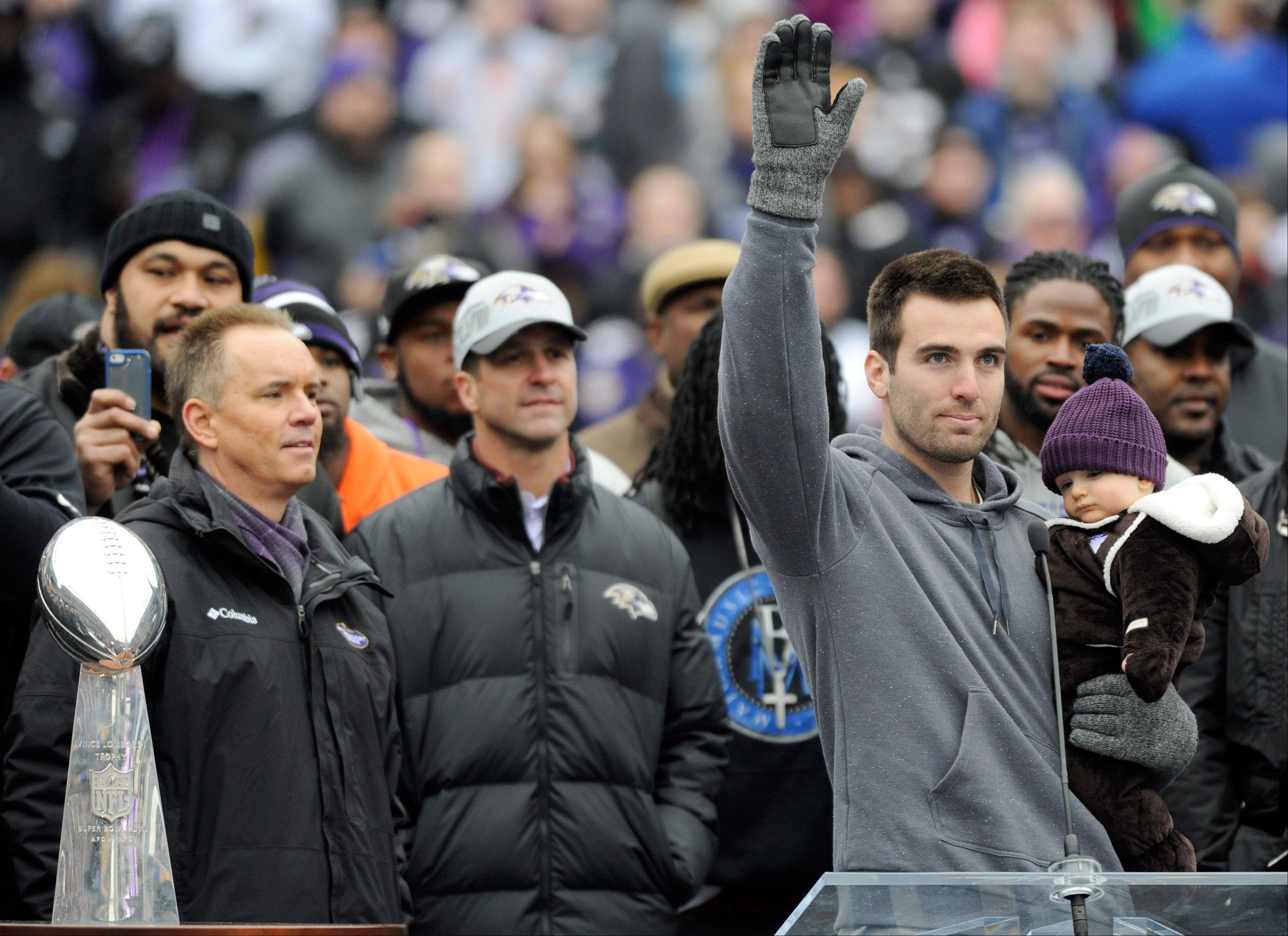 Baltimore Ravens quarterback Joe Flacco, holding his son Stephen, waves to fans during a celebration of the NFL football team's Super Bowl championship at M&T Bank Stadium in Baltimore Tuesday, Feb. 5, 2013. The Ravens defeated the San Francisco 49ers 34-31 in Super Bowl XLVII on Sunday.