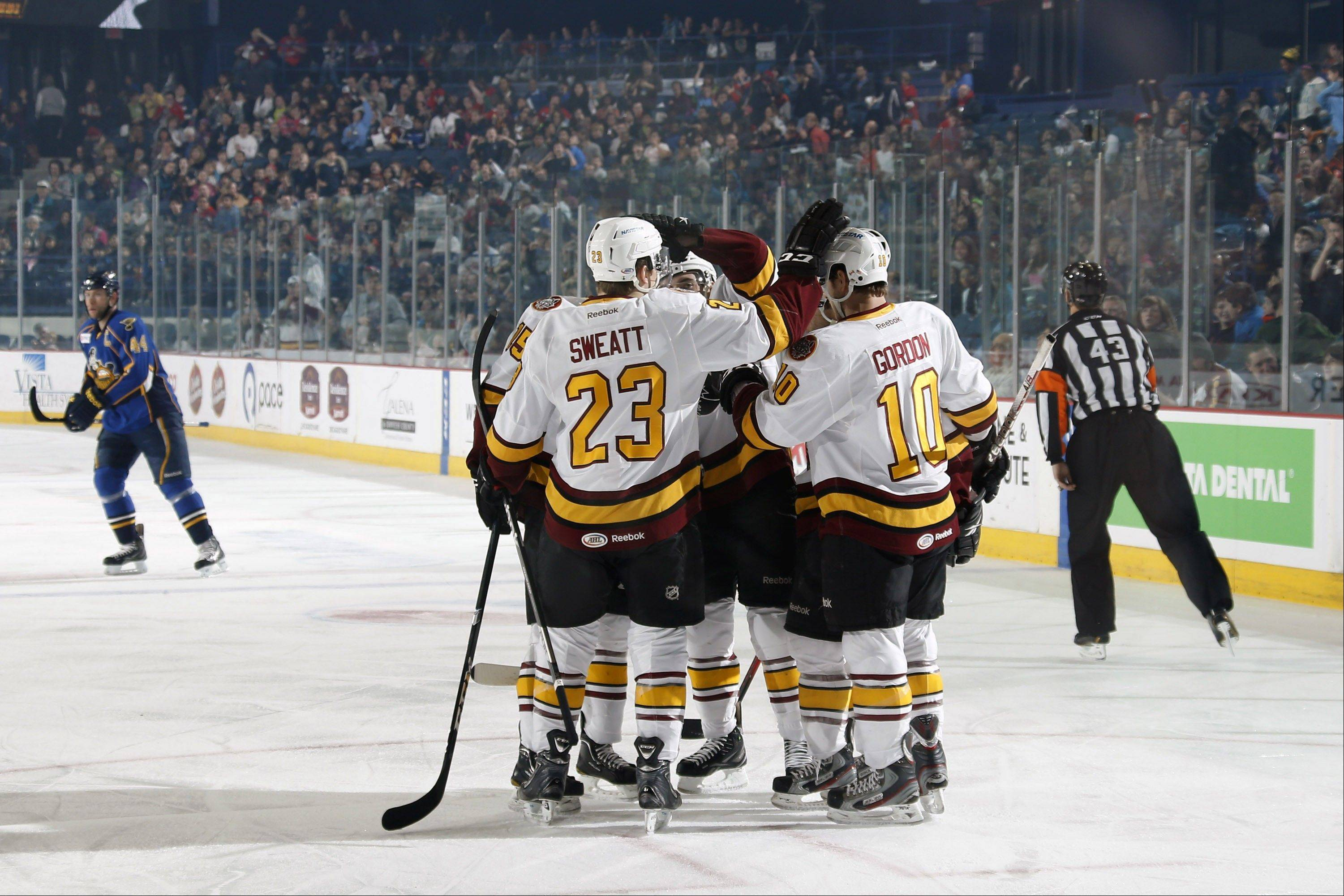 The Wolves celebrate a first period goal Tuesday against the Peoria Rivermen at Allstate Arena. The Wolves pulled out a 4-3 OT win.