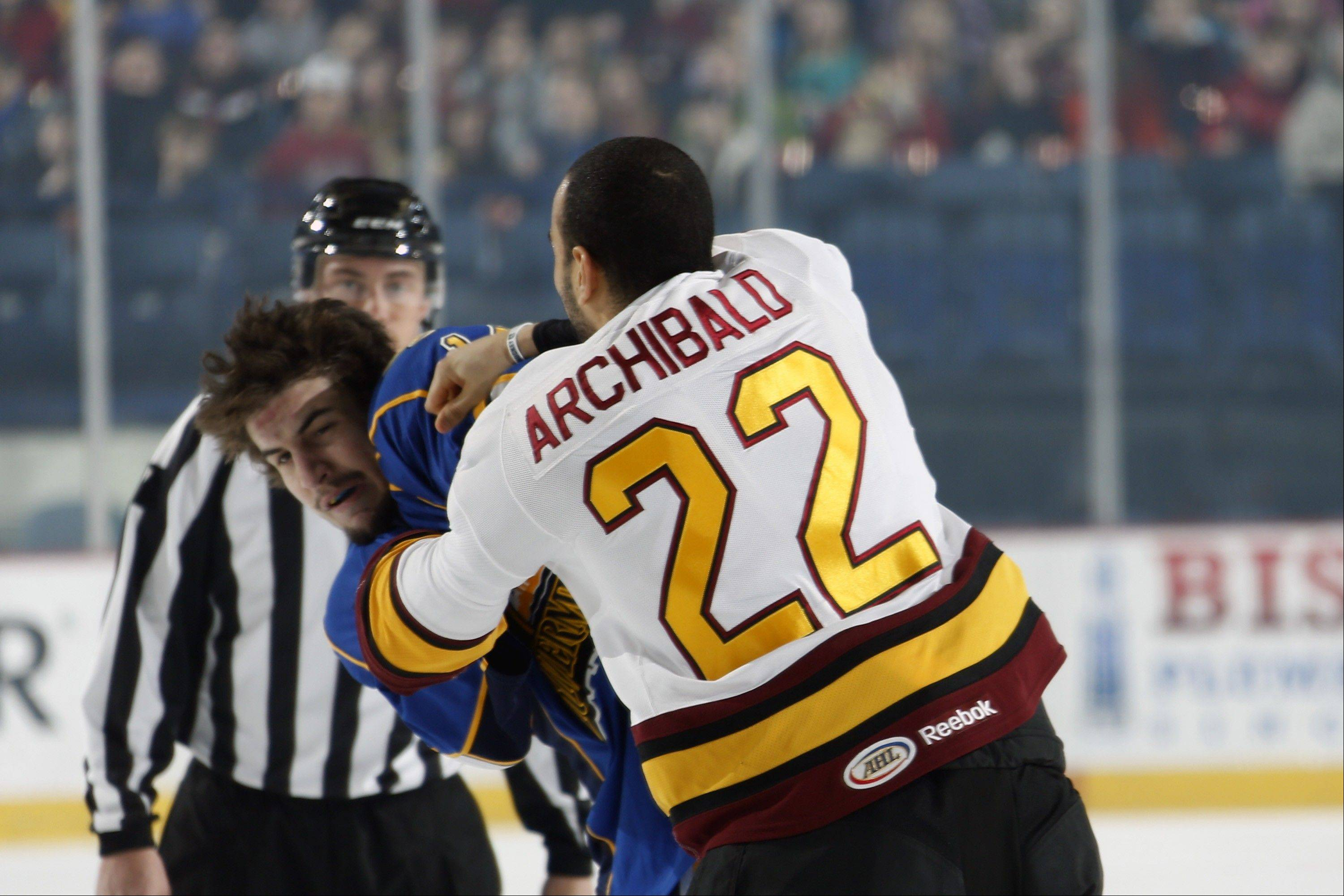 Wolves left wing Darren Archibald (22) and Peoria's Cody Beach exchange punches during Tuesday's 4-3 OT win by the Wolves at Allstate Arena.