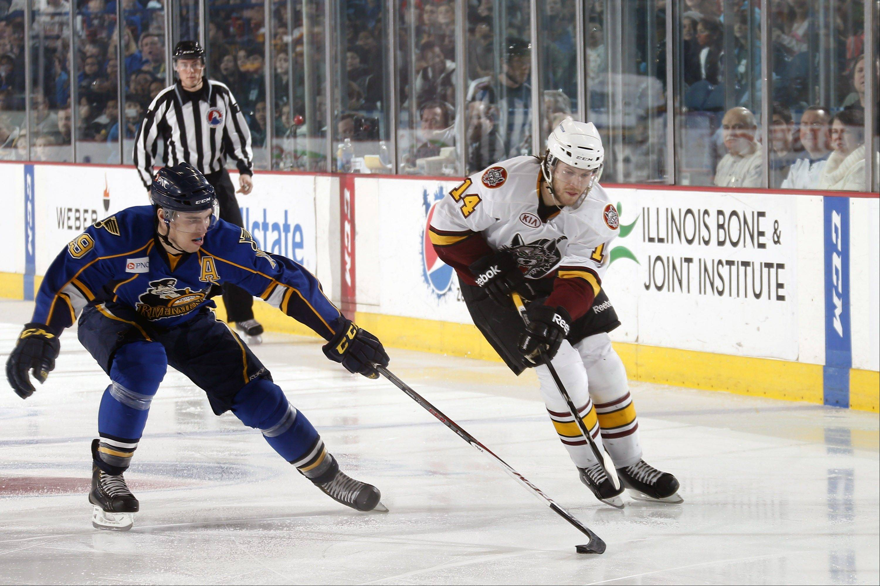 Wolves forward Tim Miller (14) and Peoria center Adam Cracknell work for position during Tuesday's 4-3 OT win by the Wolves at Allstate Arena.