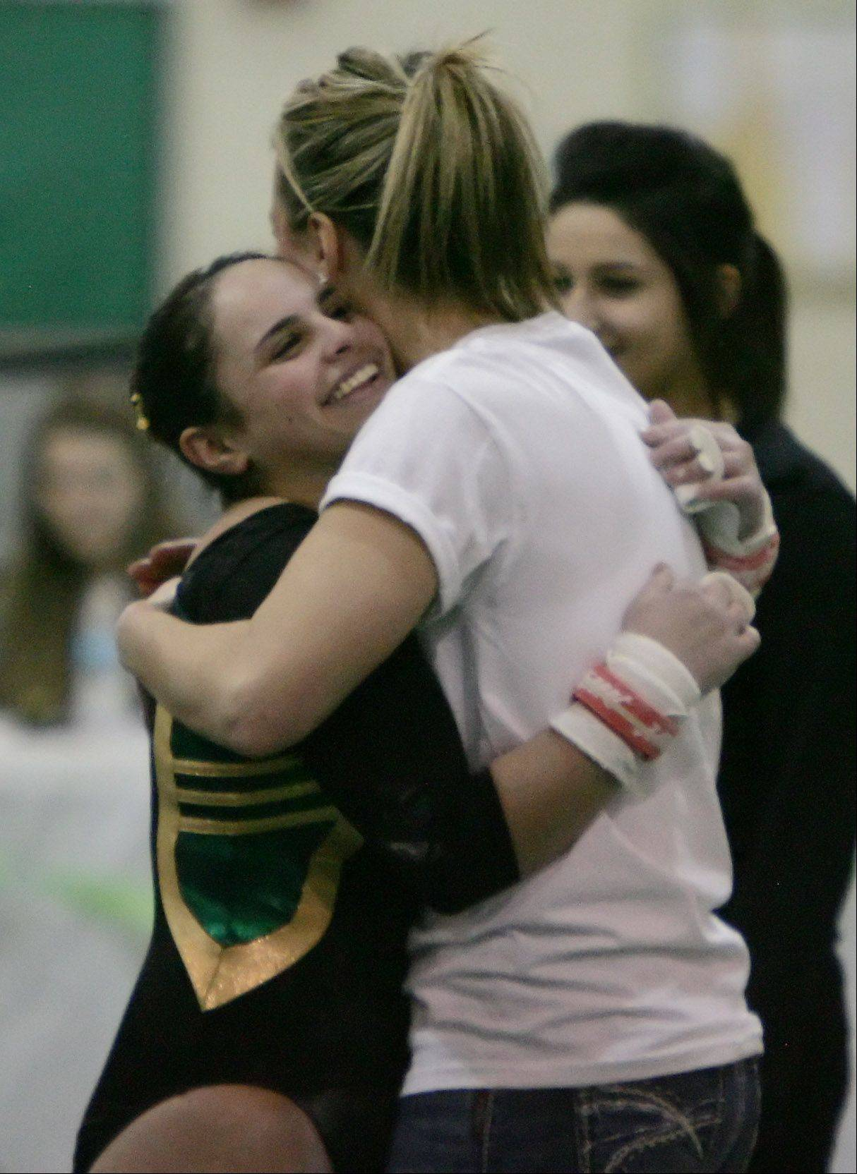 Stevenson's Alyssa Weisberg hugs assistant coach Dimitra Mullins during Thursday's gymnastics regional in Lincolnshire.