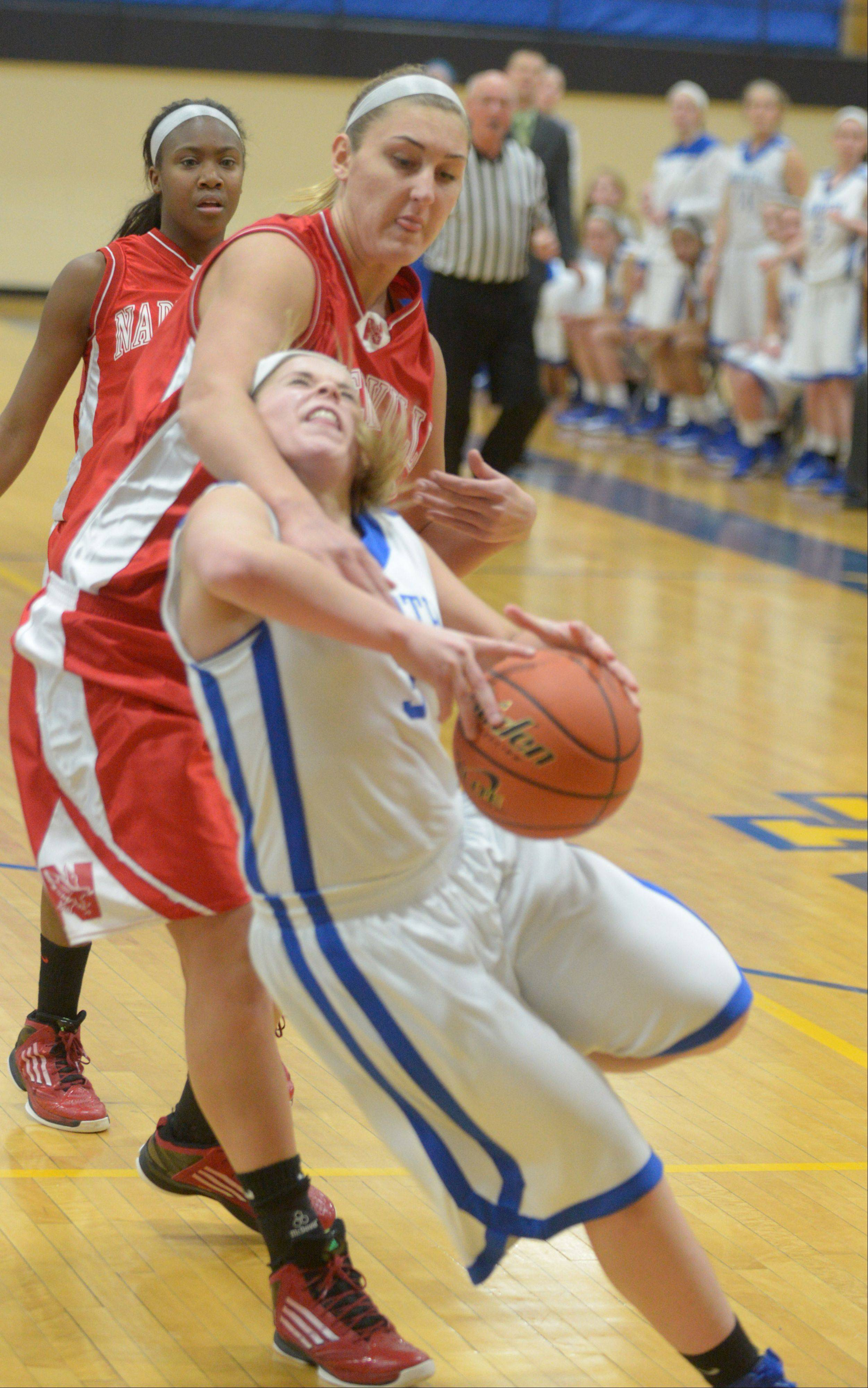 Naperville Central's Victoria Trowbridge pulls down Wheaton North's Reilly Stewart during Thursday's game.