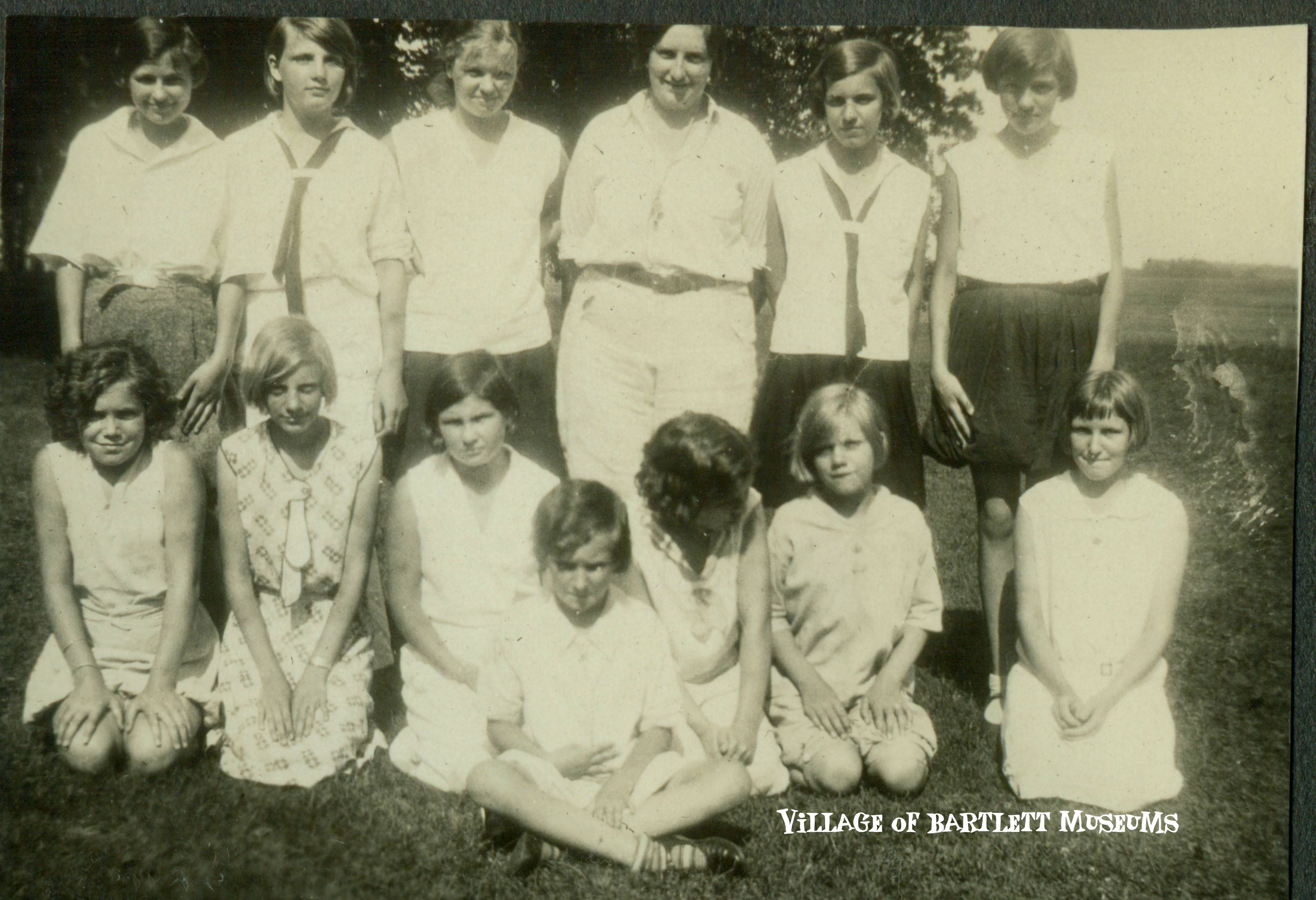 Girls Scouts were organized in Bartlett in 1929. The troop consisted of seven girls under the leadership of Estella Schnadt.    Several pages in Schnadt's personal photo album are devotes to pictures of her Bartlett Girl Scouts. This picture is identified as being taken in 1931 while the troops  was on a hike. Schnadt is in the back row third from right. Unfortunately none of the other scouts are identified in any of the images. Schnadt appreciated the outdoors and took her troop on numerous camping trips and other adventures that involved the great outdoors.