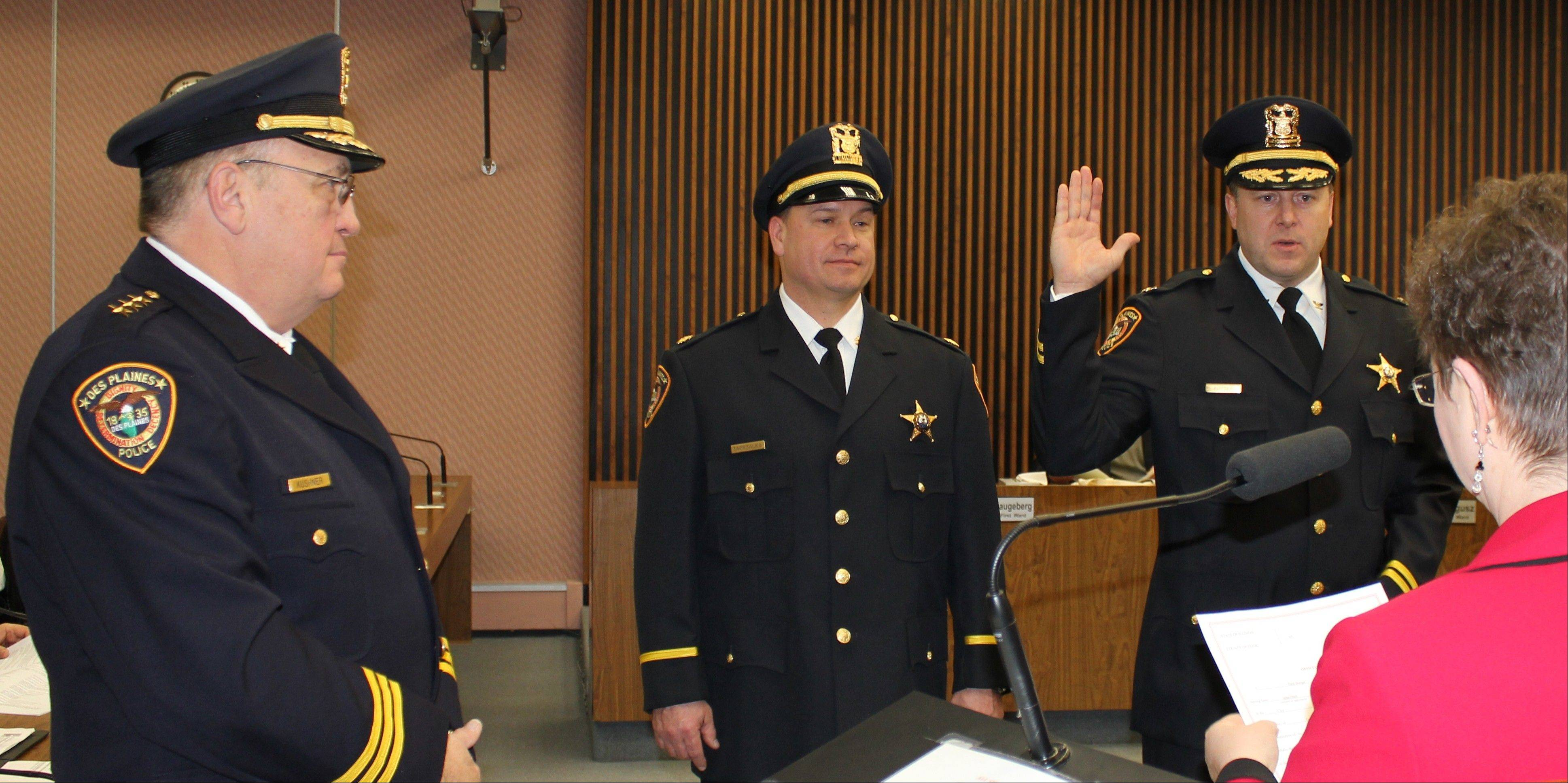 From left, Des Plaines Police Chief William Kushner and Sgt. Chester Zaprzalka listen as Cmdr. Paul Burger is sworn in as deputy chief by City Clerk Gloria Ludwig at Monday's city council meeting. Zaprzalka also was promoted to commander of support services.