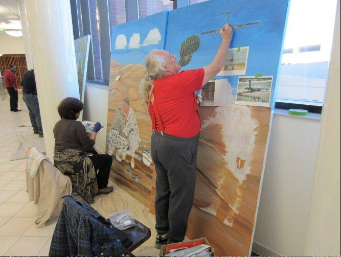 Veteran artist Richard Simmons, right, and veteran artist and Lovell FHCC employee Letty Knight work on the middle panels of the mural depicting Desert Storm.