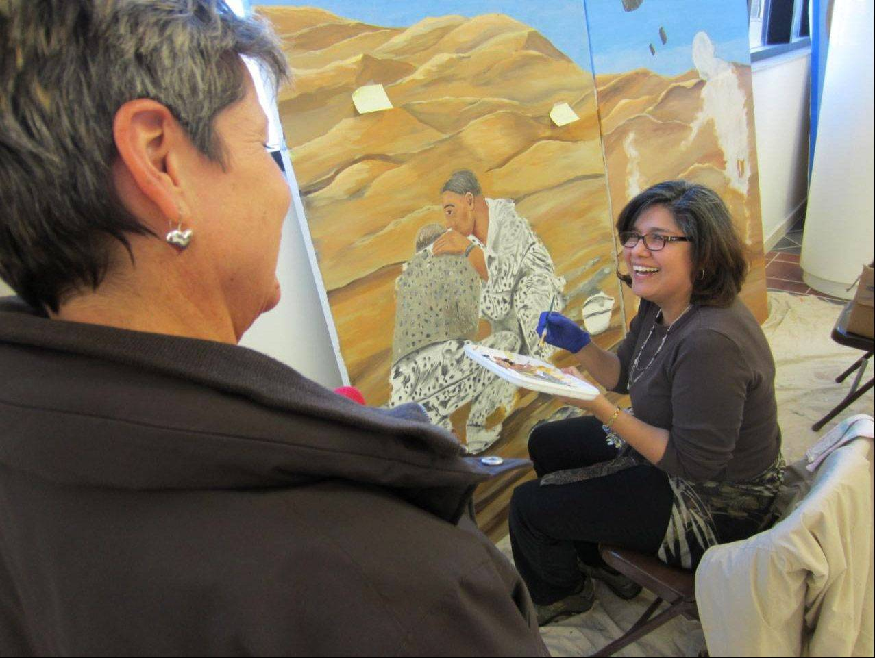 Navy veteran and Lovell FHCC employee Letty Knight, right, talks with her co-worker, Christine Misovie, about the section of the mural Knight is painting, which depicts Desert Storm.