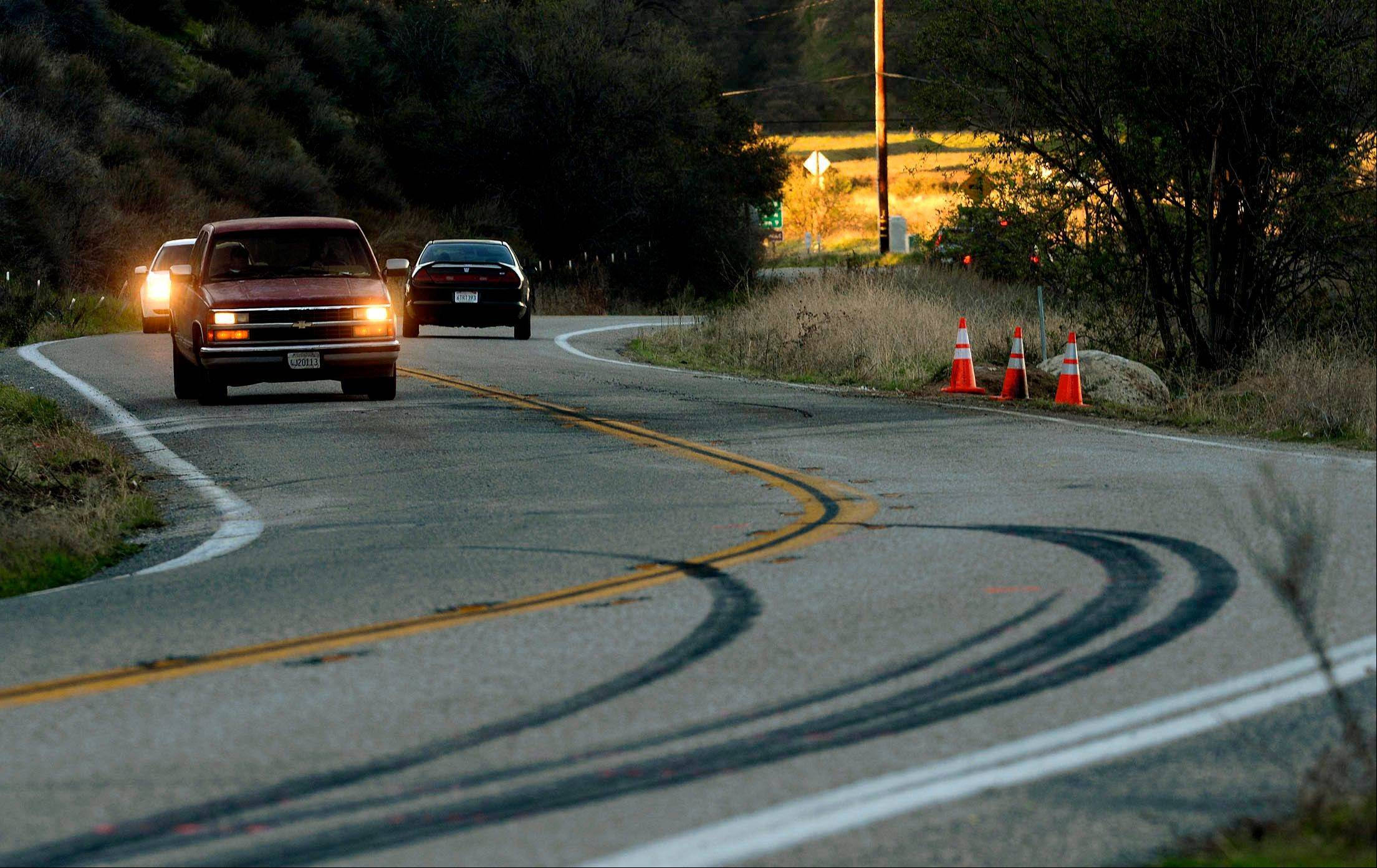 Skid marks from the weekend's fatal bus cash remain on the pavement as morning commuters drive along Highway 38 for the first time since the road was reopened, Tuesday, Feb. 5, 2013 in Yucaipa, Calif.