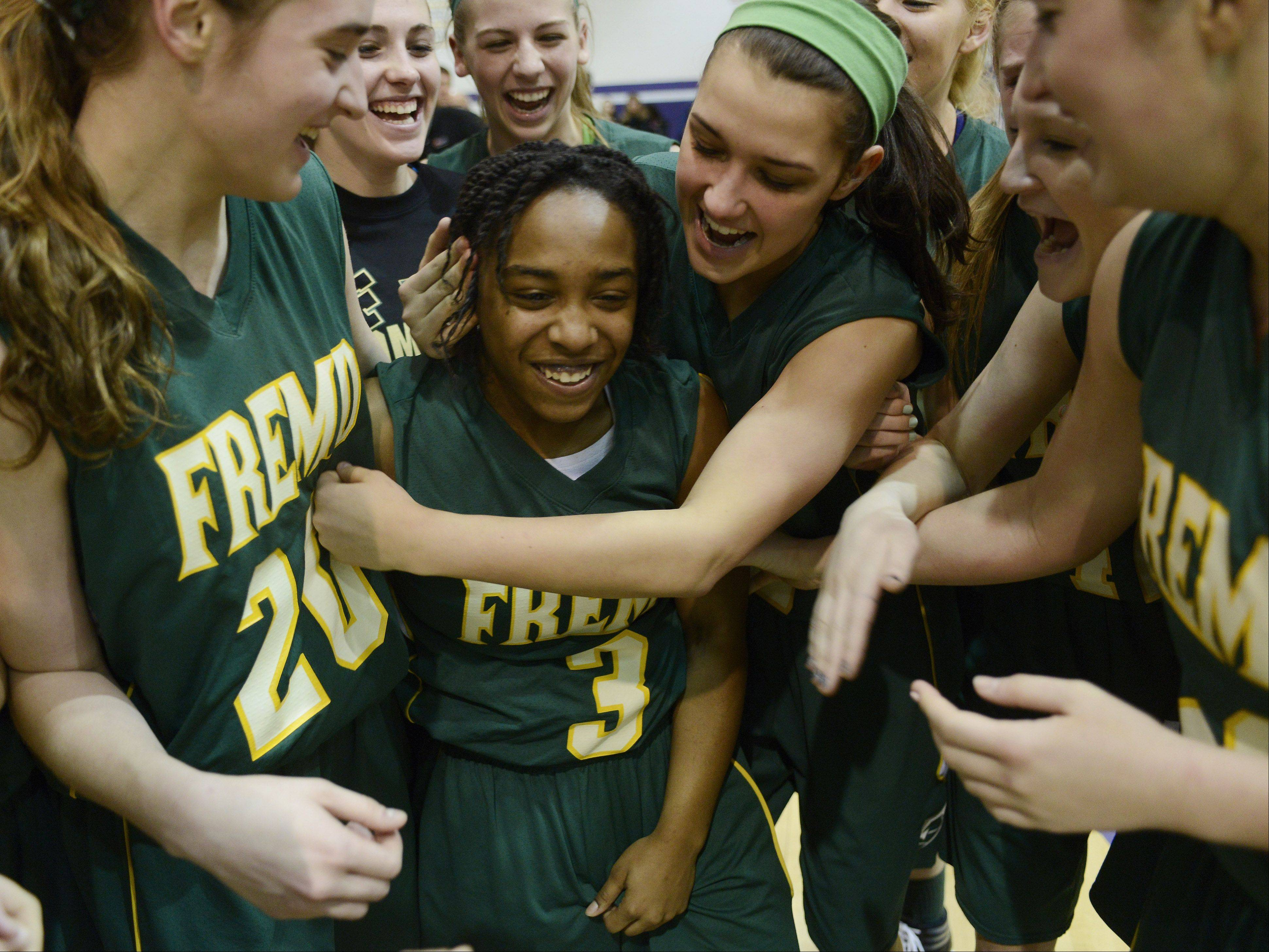 Fremd freshman Brianna Lewis, middle, is mobbed by teammates after she hit the game-winning shot in overtime to beat Rolling Meadows in the Mid-Suburban league championship game.