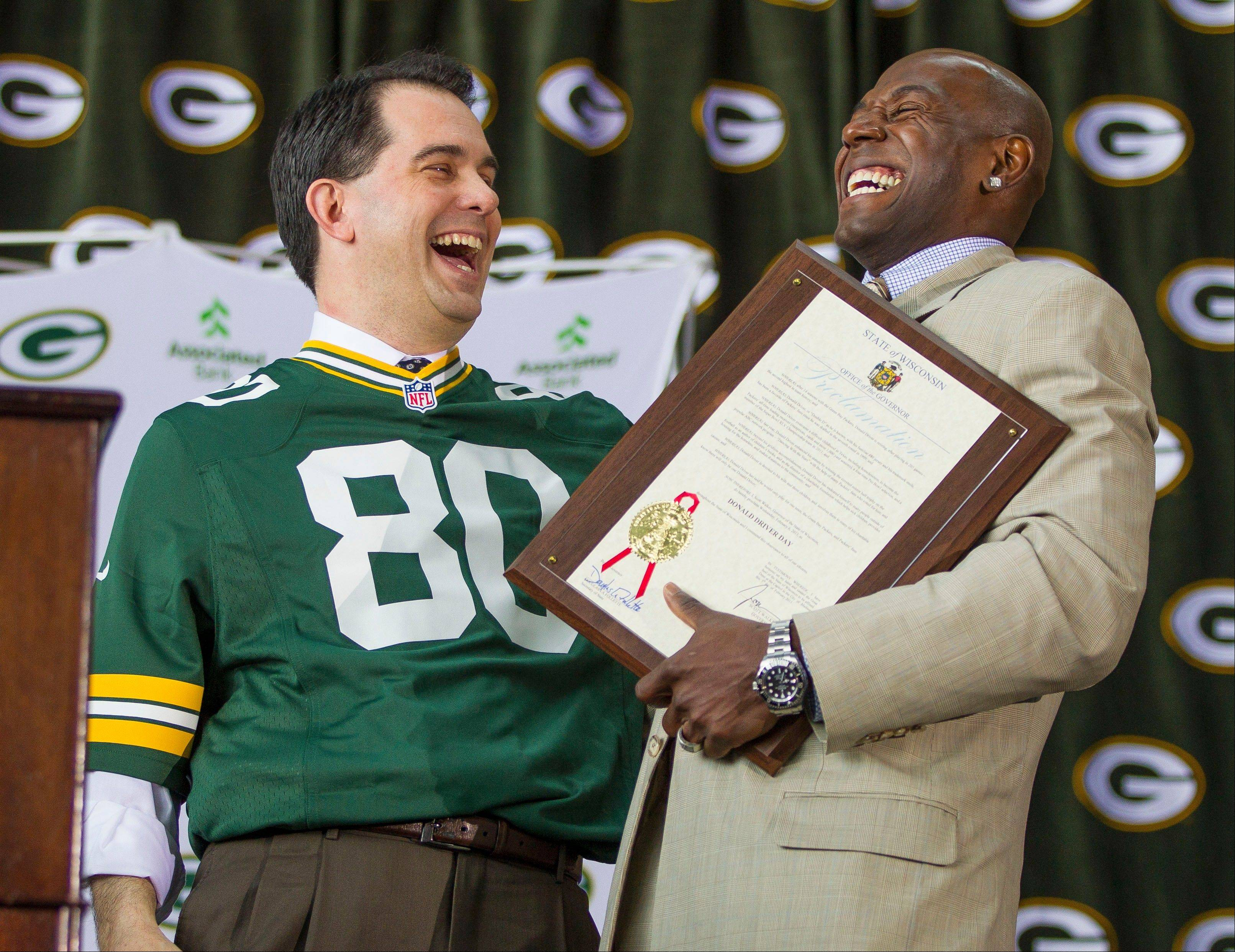 Green Packers all time leading receiver, Donald Driver, right, shares a laugh with Wisconsin Governor Scott Walker during Drivers retirement ceremony Wednesday, Feb. 6, 2013 at Lambeau Field in Green Bay, Wis. The governor had proclaimed the day Donald Driver day. (AP Photo/Mike Roemer)