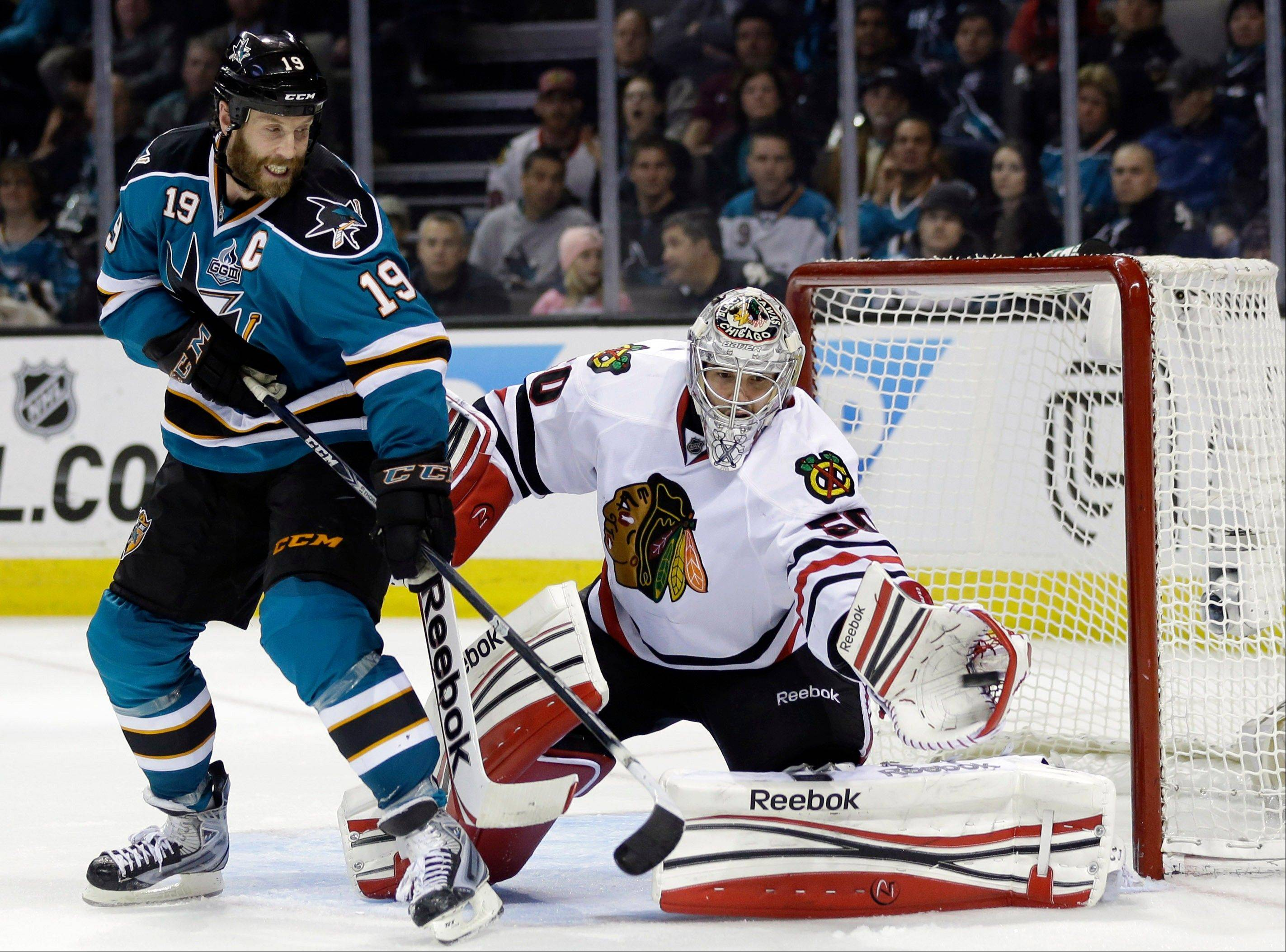 Blackhawks goalie Corey Crawford (50) stops a shot on goal next to San Jose Sharks center Joe Thornton (19) during the second period of an NHL hockey game in San Jose, Calif., Tuesday, Feb. 5, 2013.