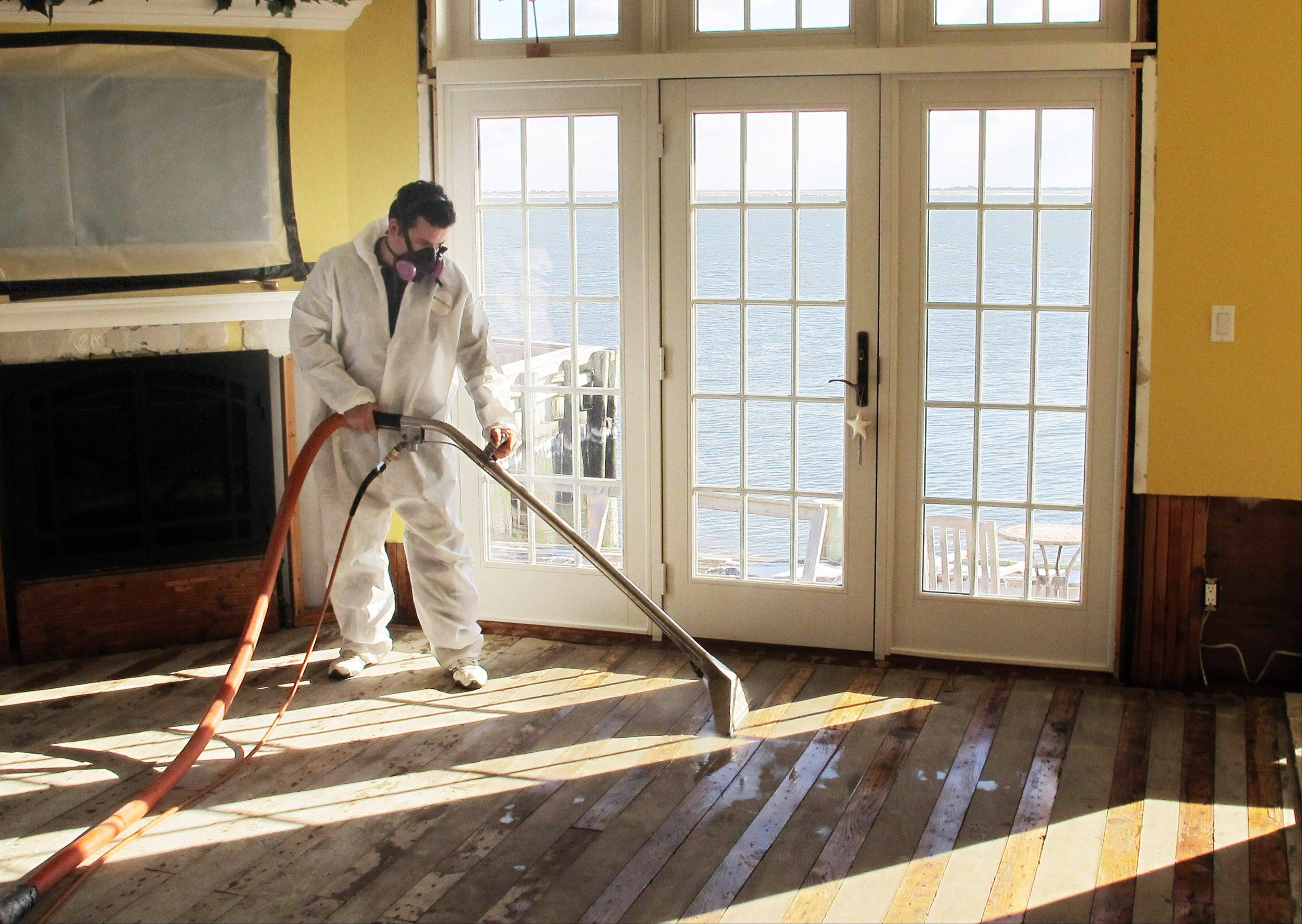 Victor Pena of Flag Enterprises steam-cleans a floor in a home in Massapequa, N.Y.