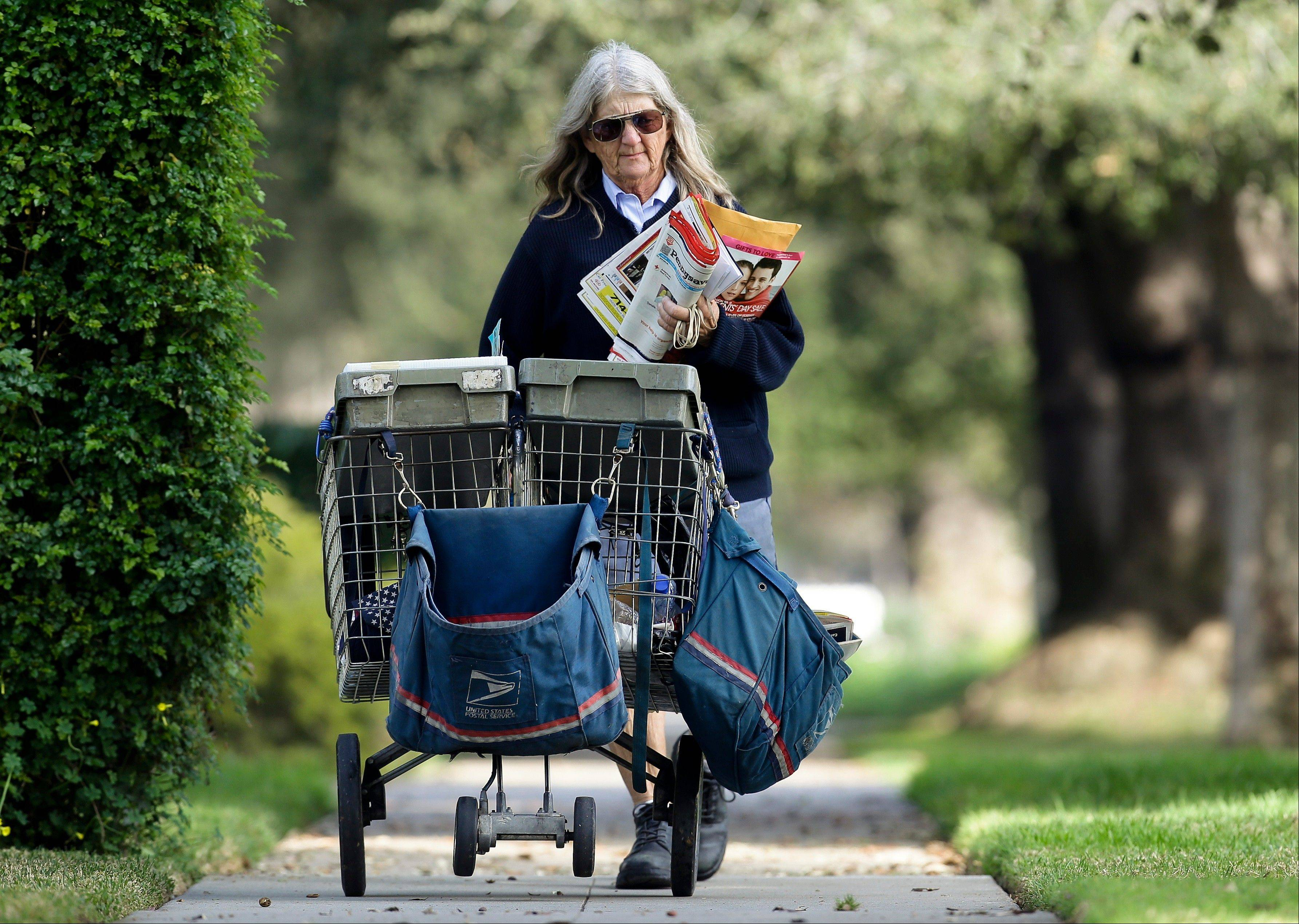 A U.S. mail carrier walks her route Wednesday in Santa Ana, Calif.