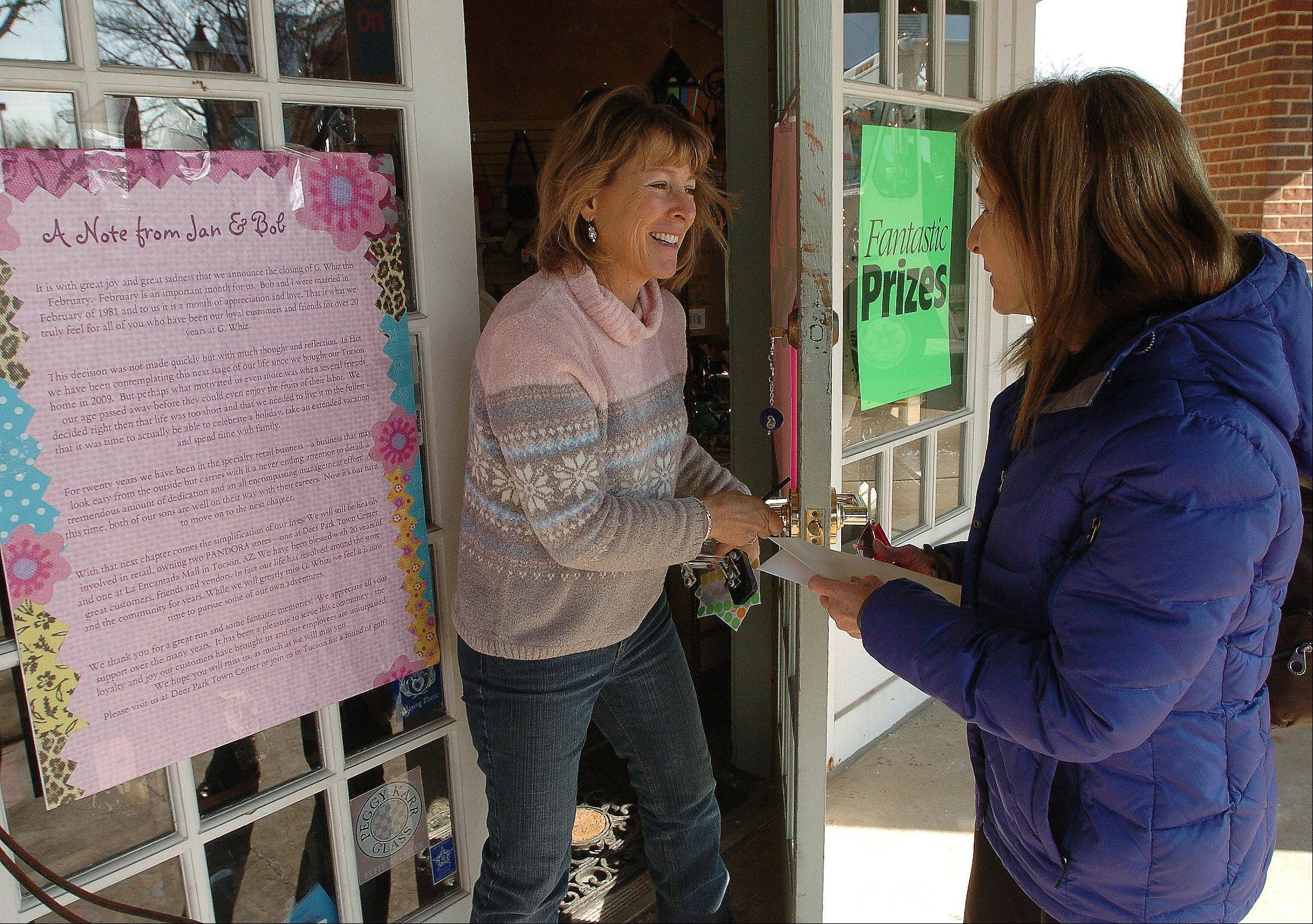 Jan Cunningham greets well-wisher Demetra Abney of Woodstock, a customer for 10 years at G. Whiz, informing her that the store will be closing its doors.