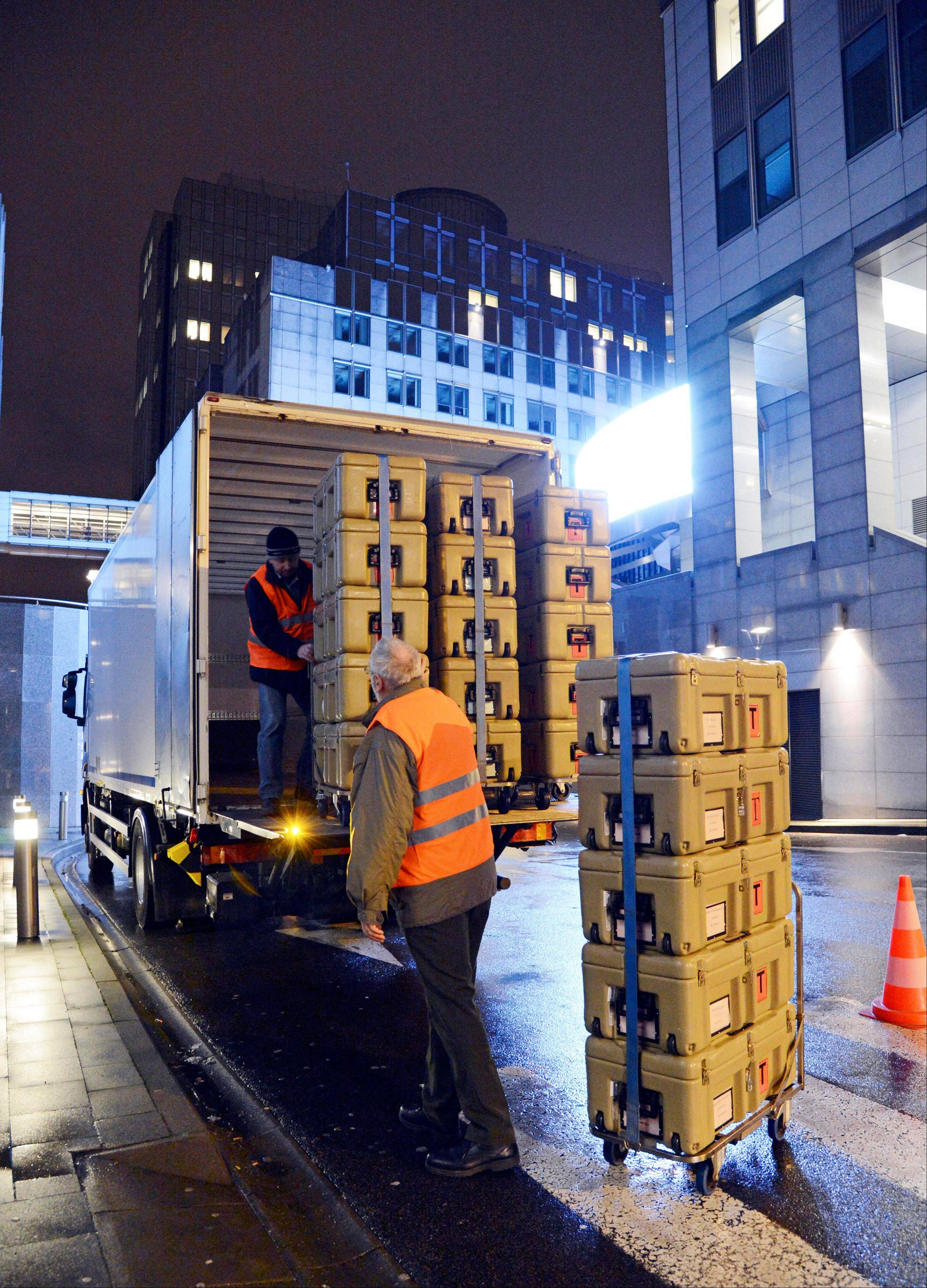 Workmen load boxes onto a truck outside the European Parliament building, in Brussels on Friday, Feb. 1, 2013, ready for transportation to Strasbourg in France.