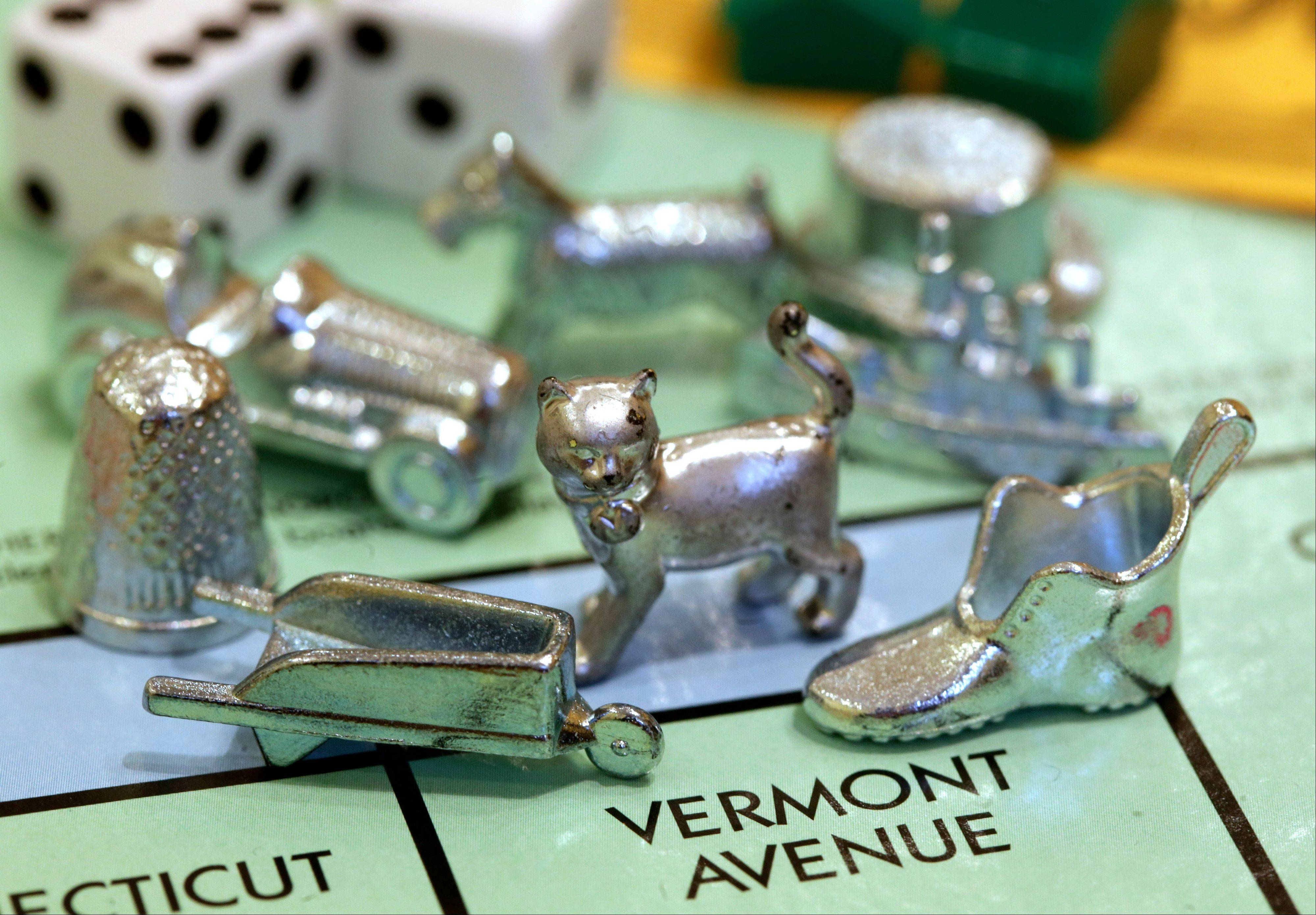 The newest Monopoly token, a cat, center, rests on a Boardwalk deed next to other tokens still in use including the wheelbarrow, left, and the shoe, right, at Hasbro Inc. headquarters, in Pawtucket, R.I., Tuesday, Feb. 5, 2013. Voting on Facebook determined that the cat would replace the iron token.