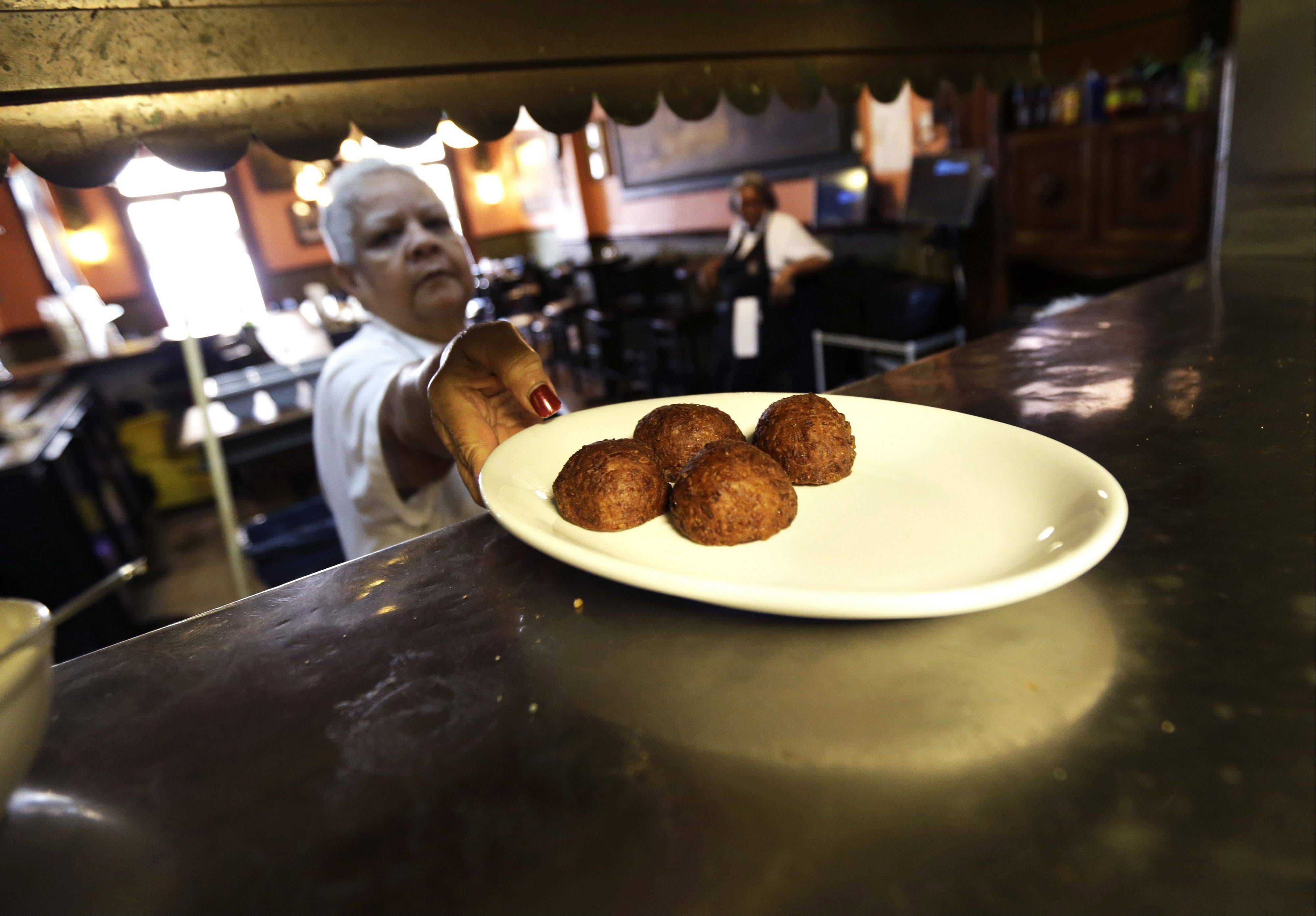 Waitress Gaynell James serves up calas cake from the kitchen at The Old Coffeepot Restaurant in the French Quarter of New Orleans. Calas, tangy rice fritters born to go with cafe au lait.