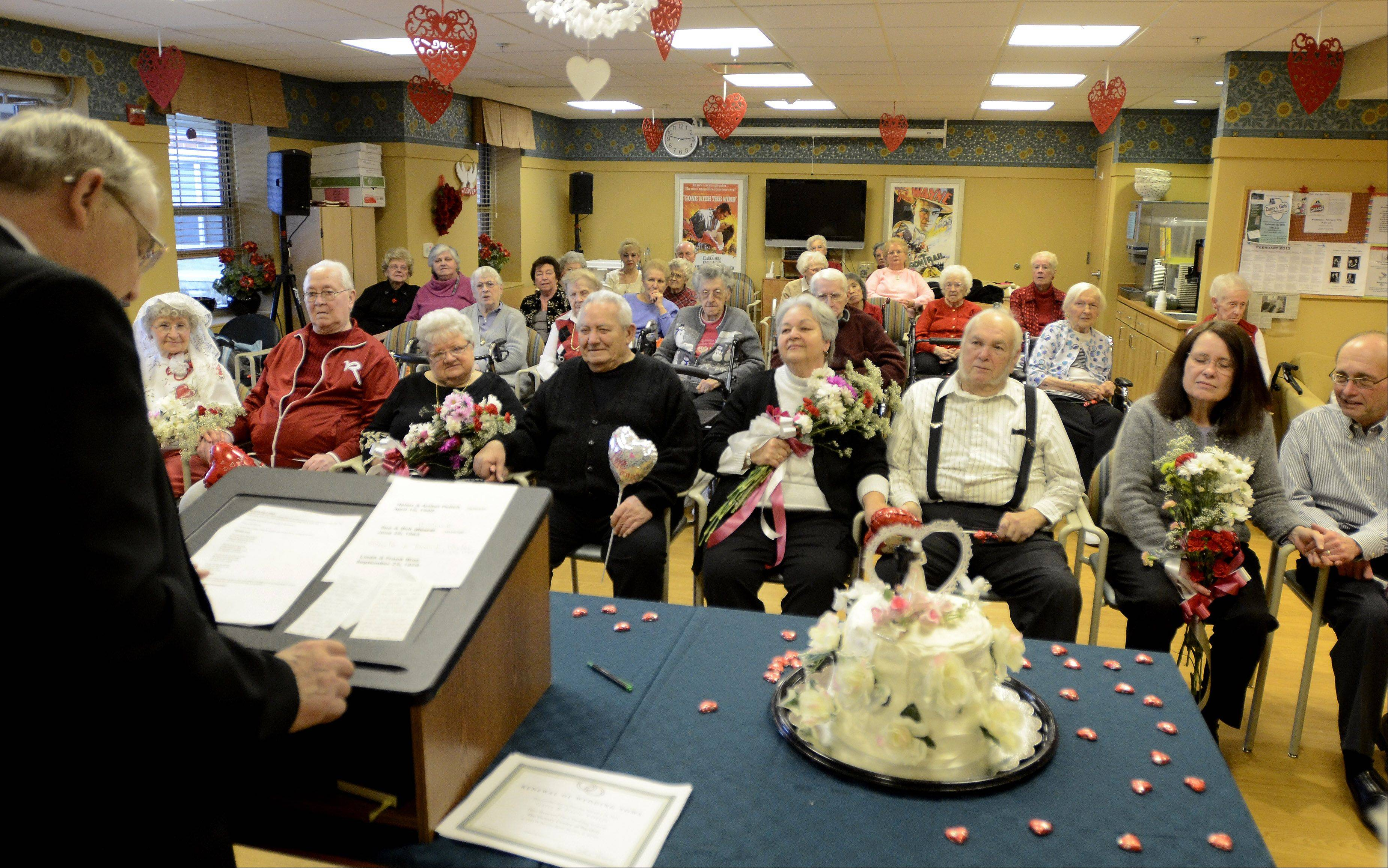 The Rev. Elder Dale presides over couples from left, Helen and Arthur Polich, Sue and Bob Richardi, Gayle and David Voyles and Linda and Frank Broz, who celebrated Valentine's Day by renewing their wedding vows Thursday at Victory Centre of Bartlett.