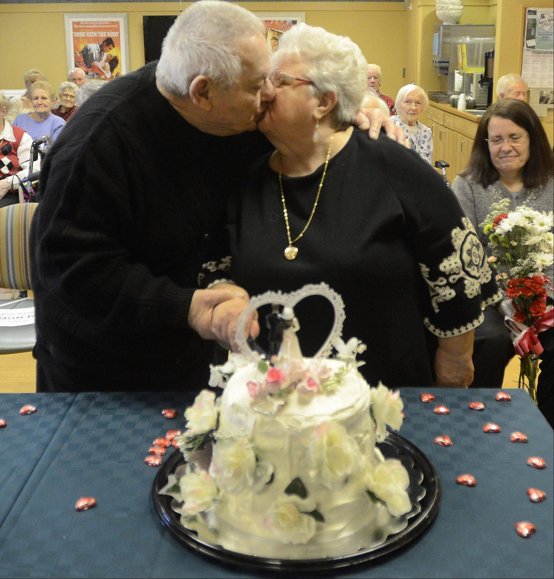 Sue and Bob Richardi kiss while cutting the cake after they and other couples at Victory Centre of Bartlett marked Valentine's Day by renewing their wedding vows.