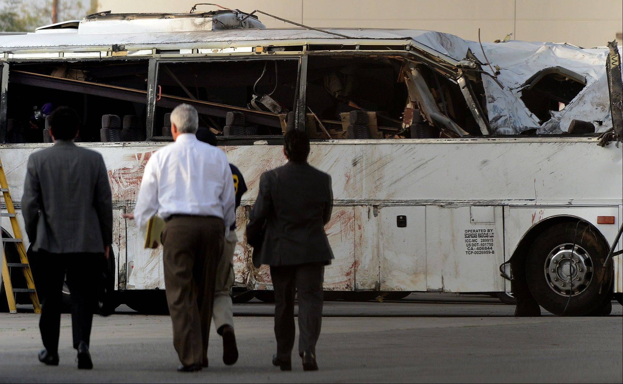 National Transportation Safety Board members walk toward the bus crash site Tuesday, Feb. 5, 2013, in Ontario, Calif., before giving an update on the investigation of Sunday's tour bus crash near Yucaipa that killed eight people.