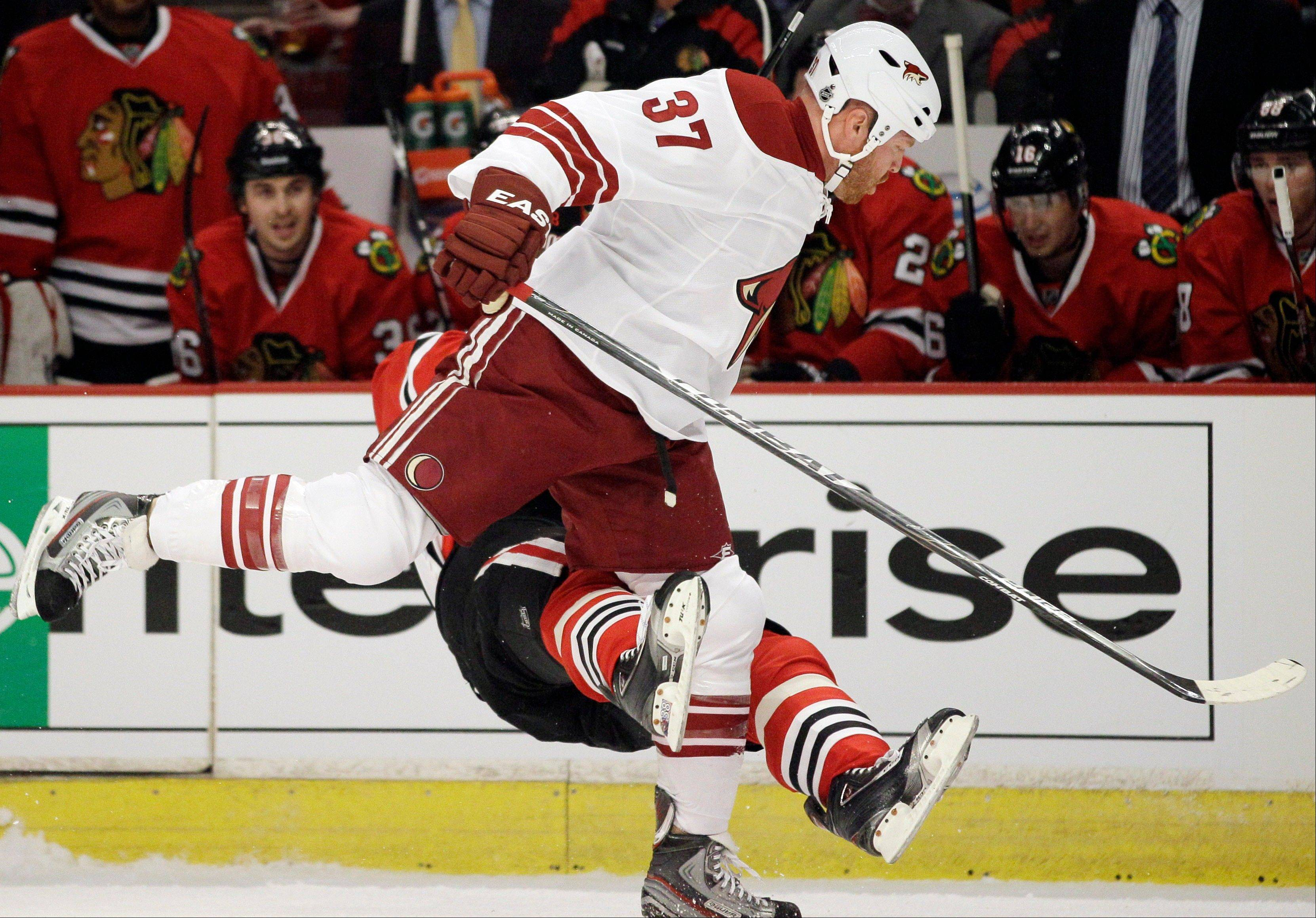 The Hawks' Marian Hossa falls down after getting checked by the Coyotes' Raffi Torres during the first period of Game 3 of their first-round playoff series at the United Center.