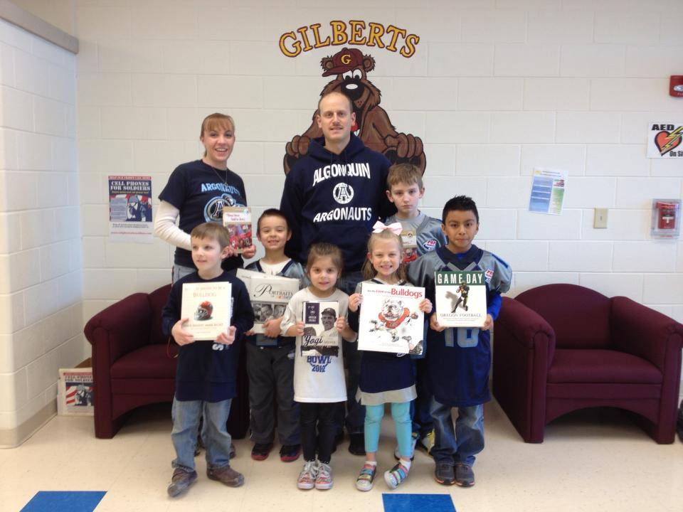 Argonauts players, parents and cheerleaders present Gilberts Elementary with 25 new hardcover books