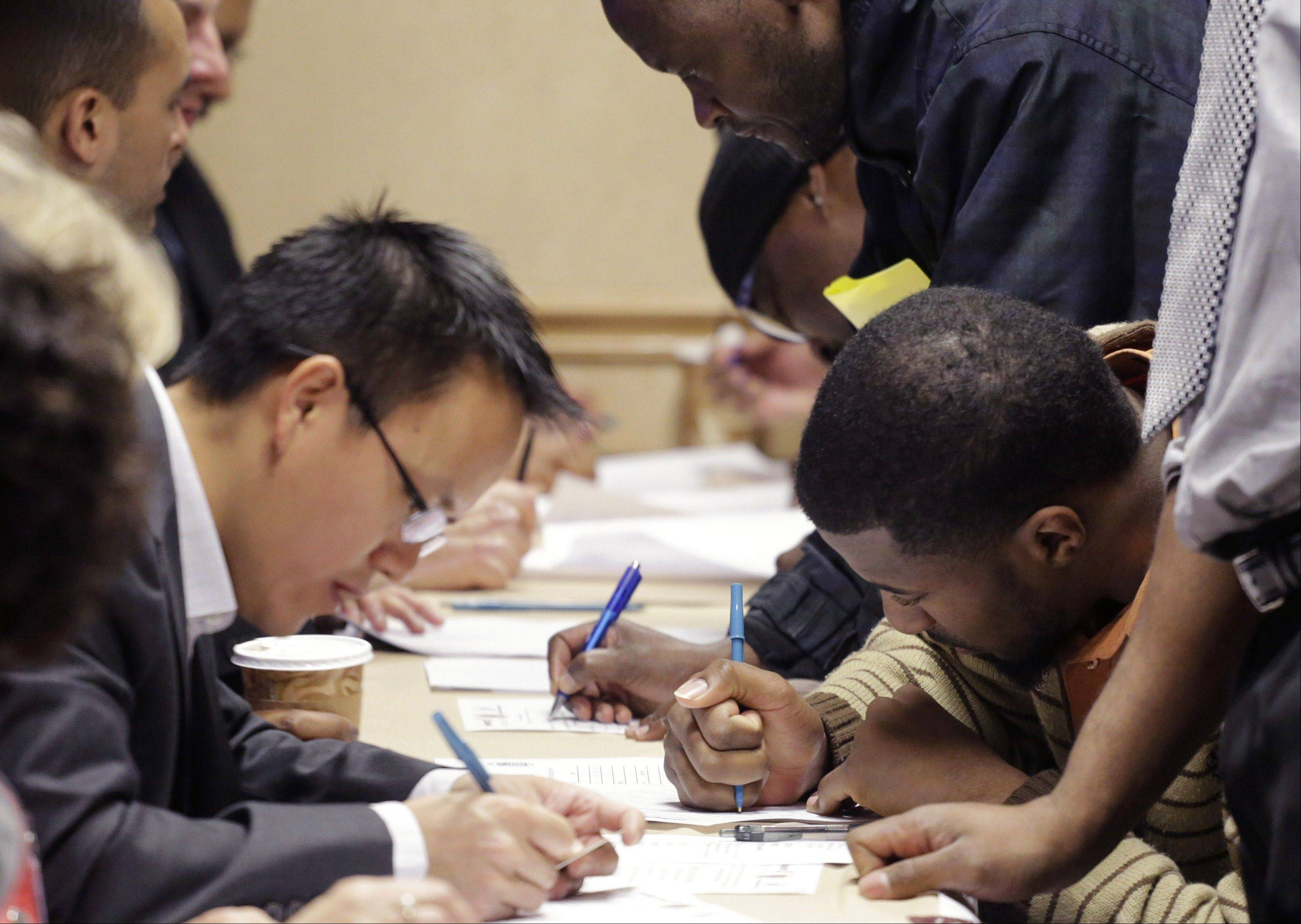 Job applicants complete forms at a job fair sponsored by Swissport, in Newark N.J.