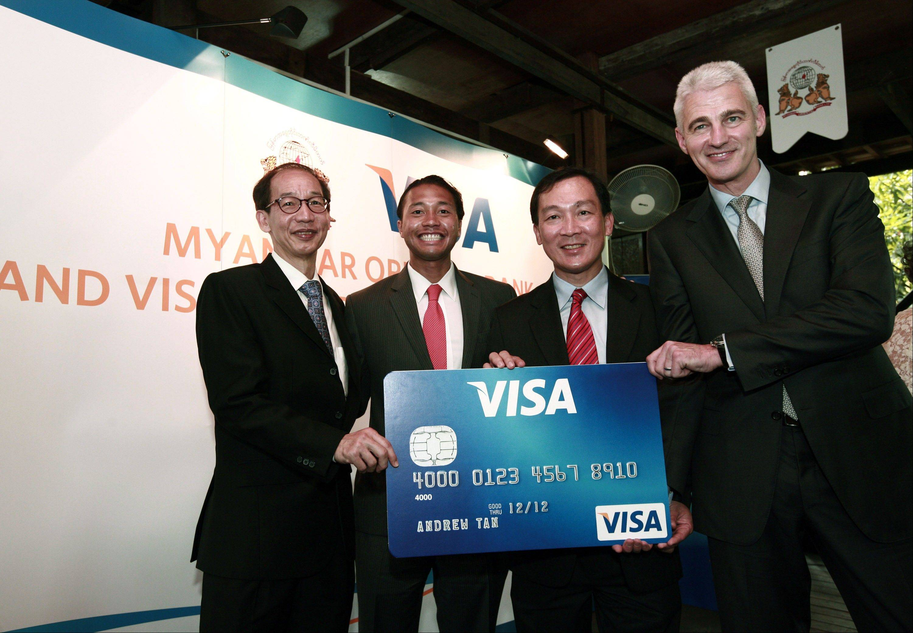 Paul Cook, right, head of Acceptance for Visa in Asia Pacific, central Europe, Middle East and Africa; Somboon Krobteeranon, second from right, country manager of Myanmar and Thailand; and two unidentified officials pose for photo with an oversized Visa card during a launching ceremony of the use of Visa cards for payments in Myanmar.