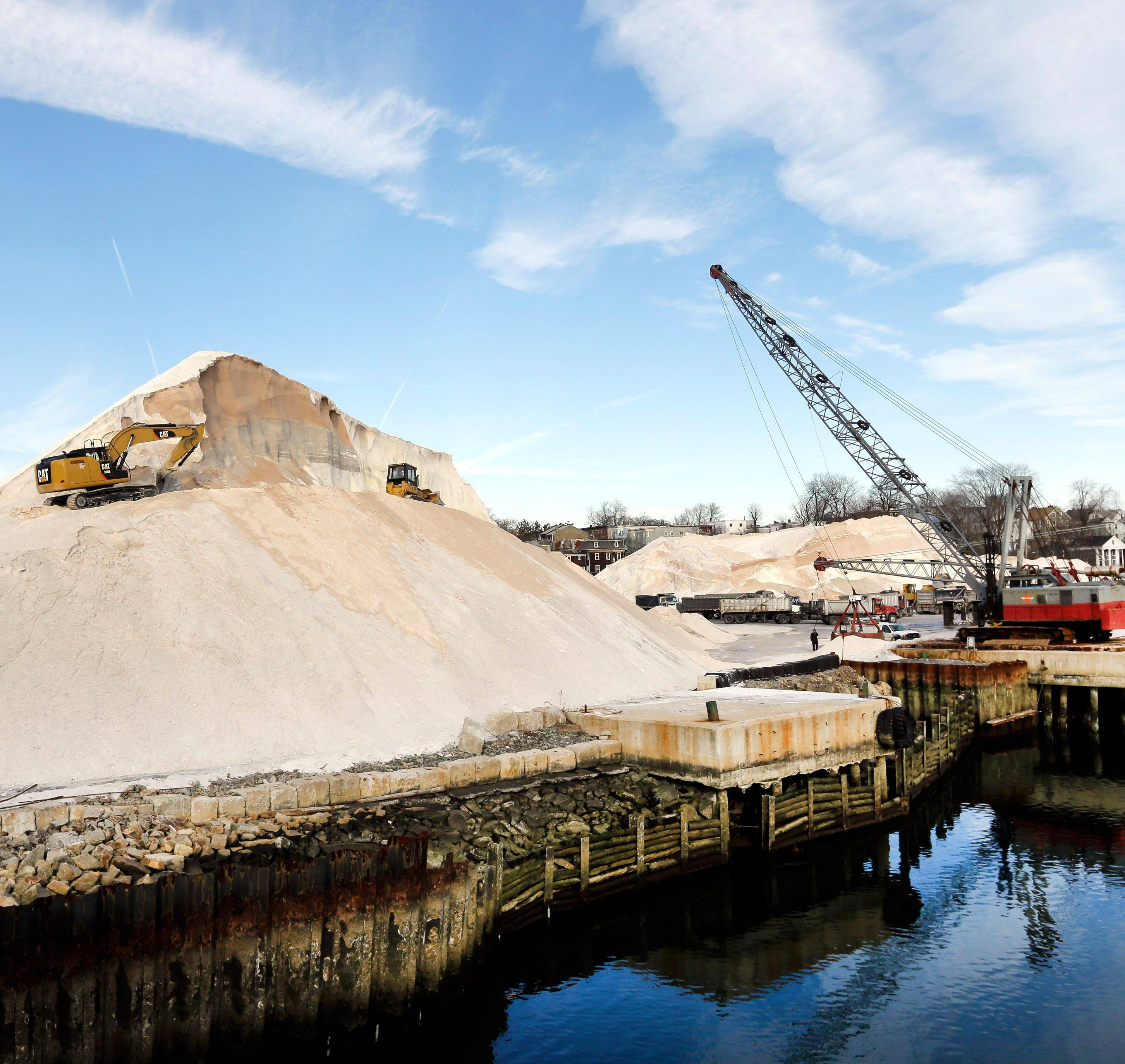 Work is ongoing on large salt piles at Eastern Salt Company in Chelsea, Mass., Thursday in preparation for a major winter storm headed toward the Northeast.