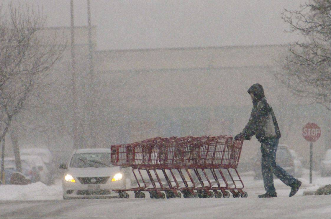 An employee at Trader Joe's in Arlington Heights rolls shopping carts through the parking lot late Thursday afternoon as the rain turned to snow.