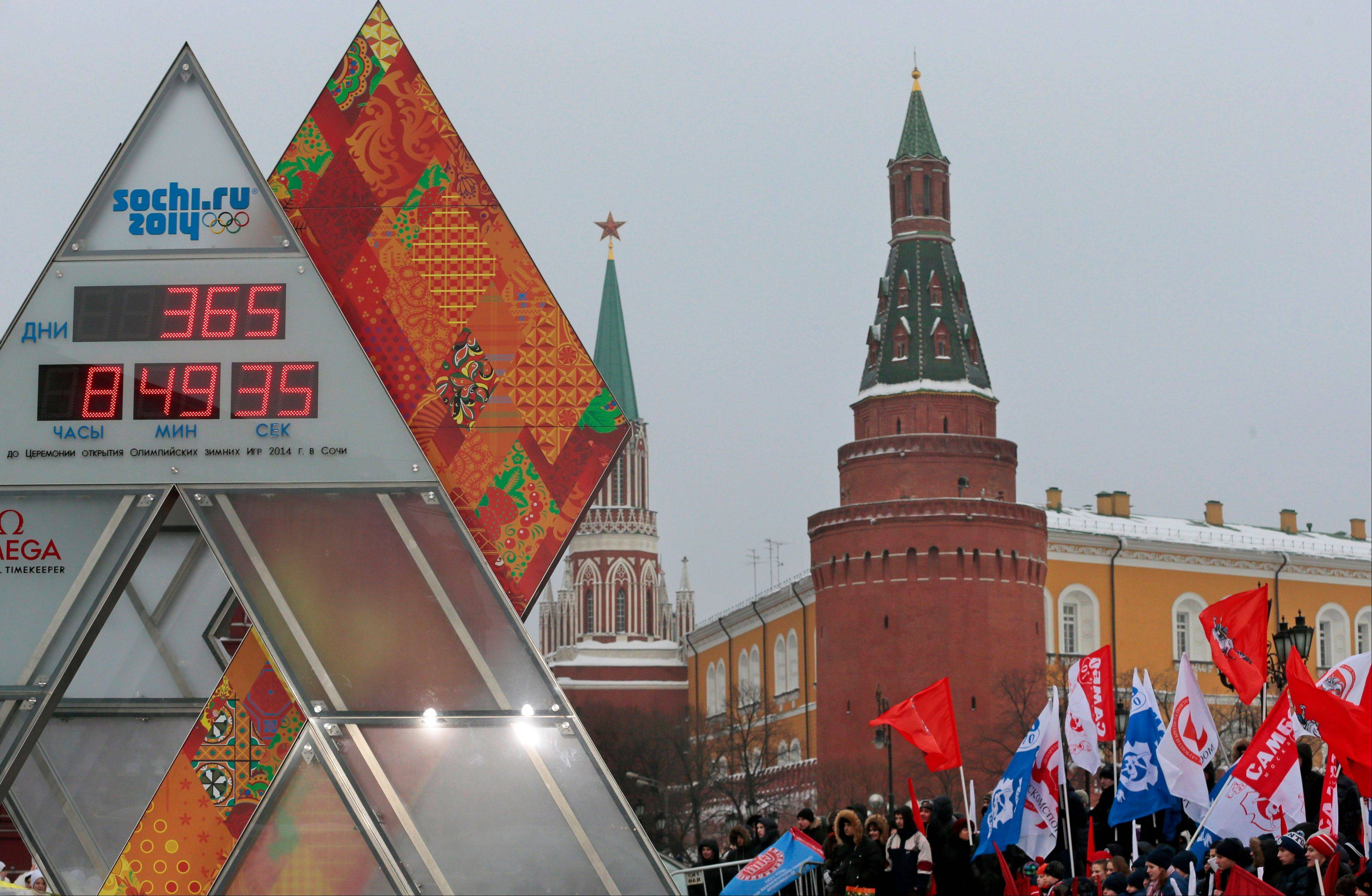 A crowd of sports enthusiasts waving Russian and Moscow flags surround the one-year countdown clock for the upcoming 2014 Sochi Olympics in Moscow, Russia.