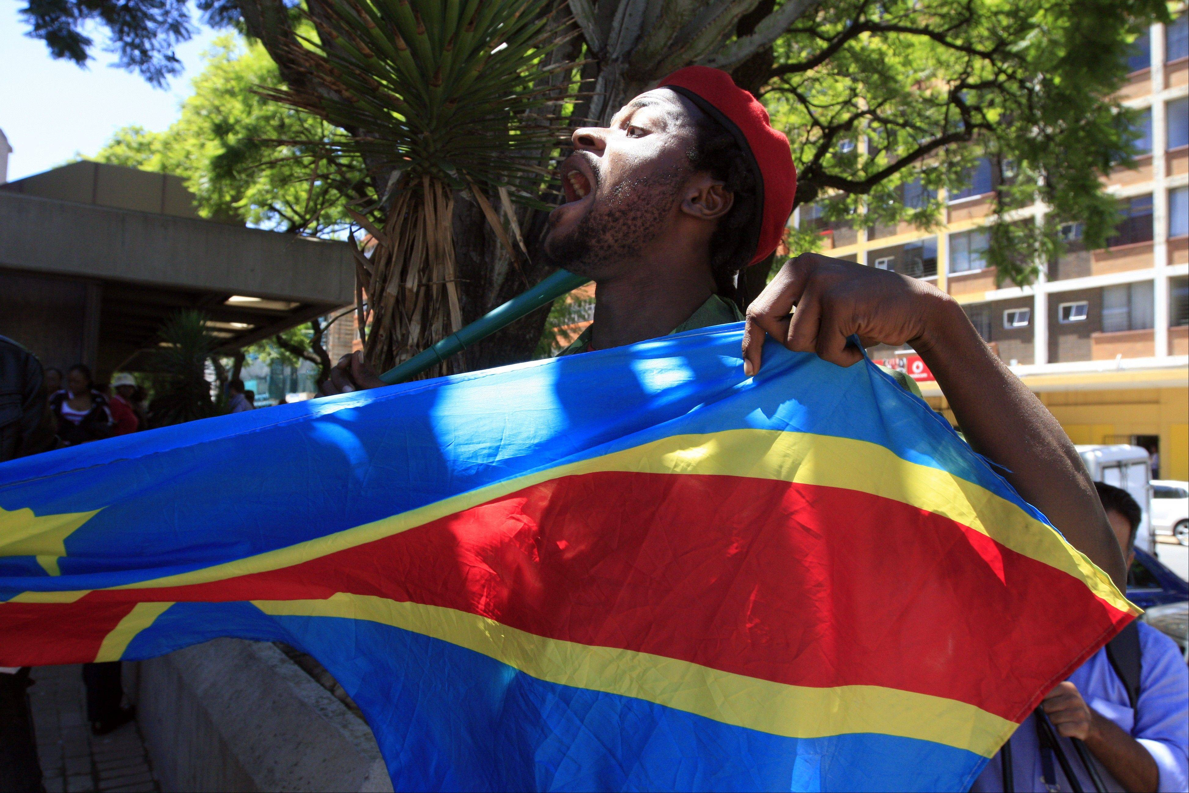 A supporter holds a Democratic Repupublic of Congo flag outside the court in Pretoria, South Africa, on Thursday, Feb. 7, 2013. Nineteen alleged members of a Congolese rebel group -- including one U.S. citizen -- sought help in their effort to overthrow Congolese President Joseph Kabila, offering mining rights in their resource-rich country in exchange for weapons and training, a prosecutor said Thursday.
