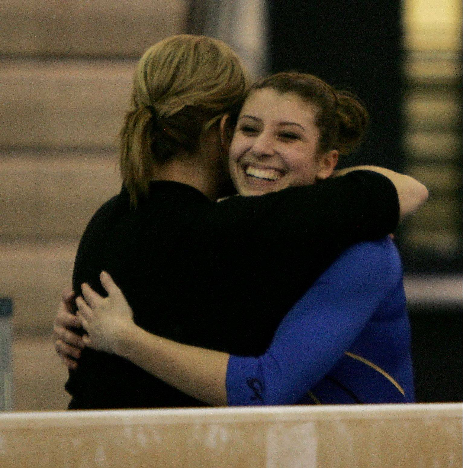 Warren's Kelsey Stoecker is hugged by her coach after balance beam.