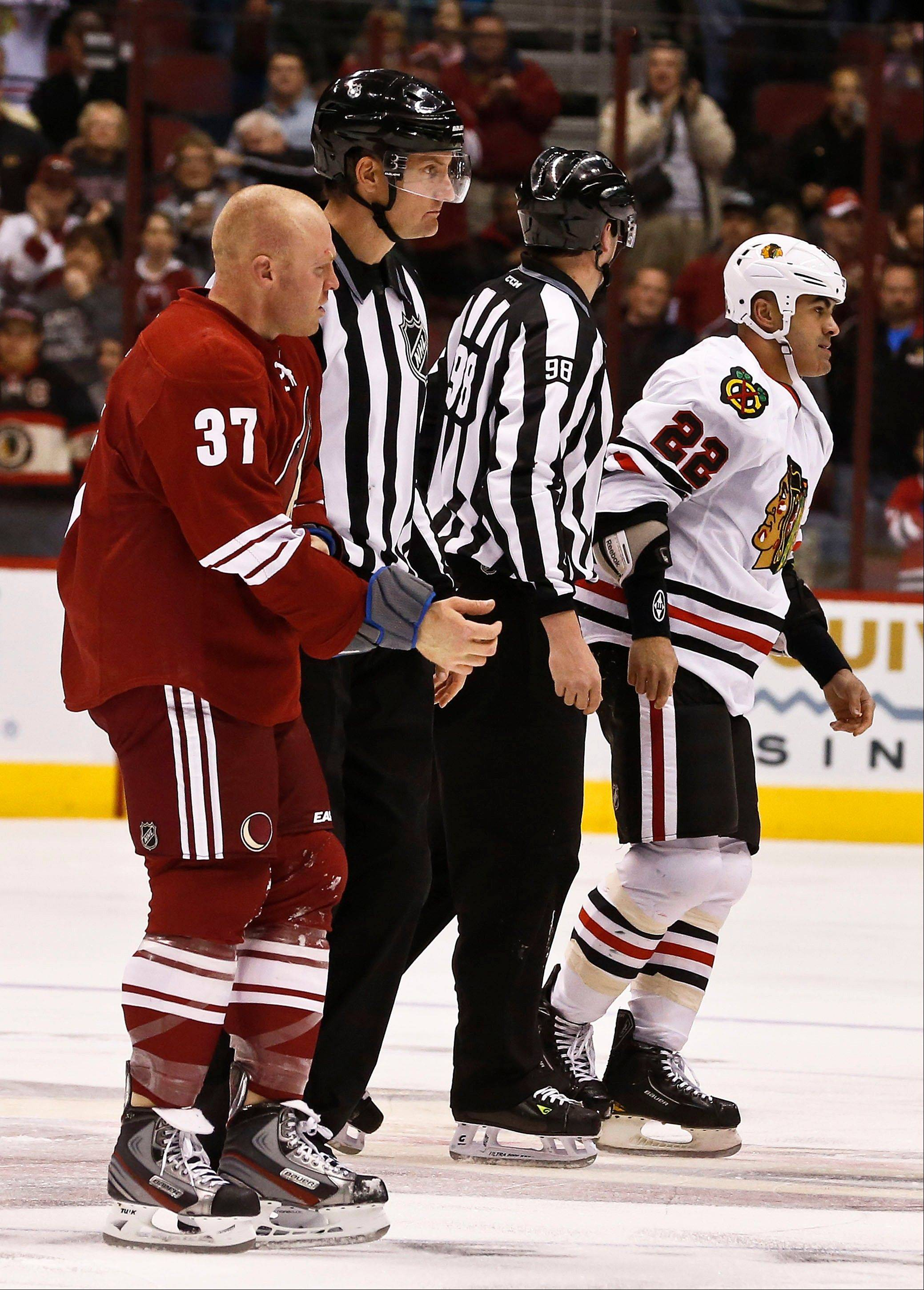 Phoenix Coyotes' Raffi Torres and Jamal Mayers are taken to the penalty box by linesmen John Grandt (98) and Shane Heyer after their first period fight Thursday.