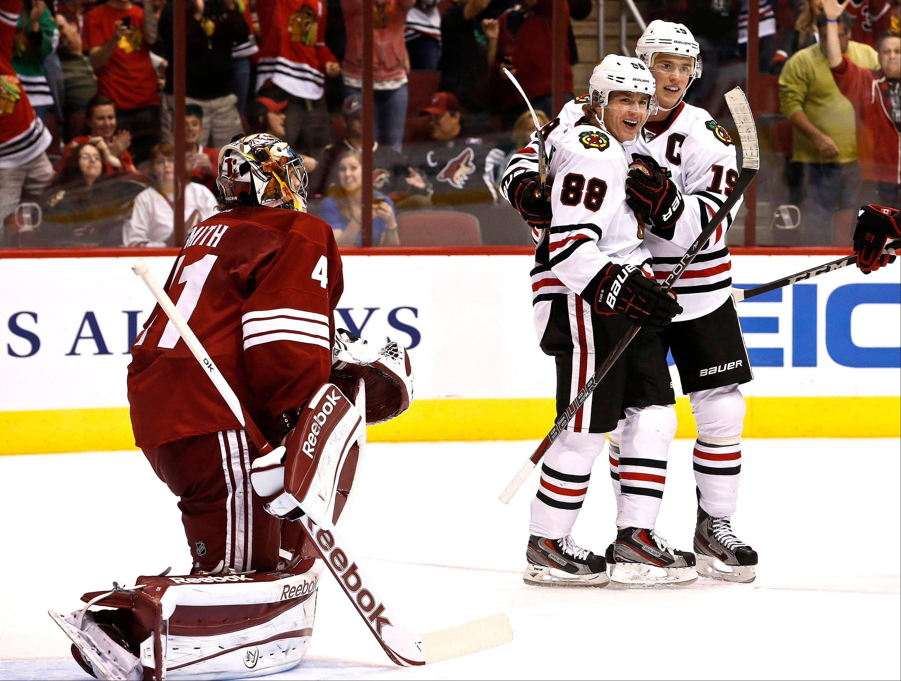 Patrick Kane celebrates his second goal against Phoenix Coyotes' Mike Smith, with Blackhawks captain Jonathan Toews Thursday.