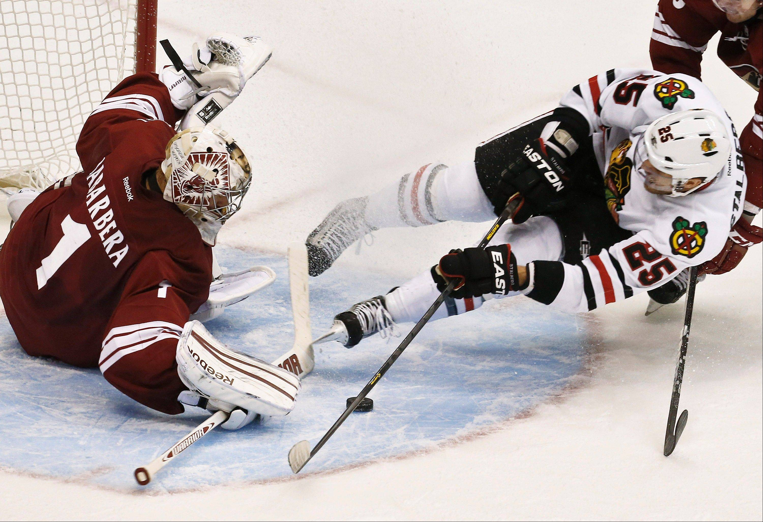 Viktor Stalberg of the Blackhawks tries to gets a shot off as he falls down in front of Phoenix Coyotes' Jason LaBarbera during the third period Thursday.