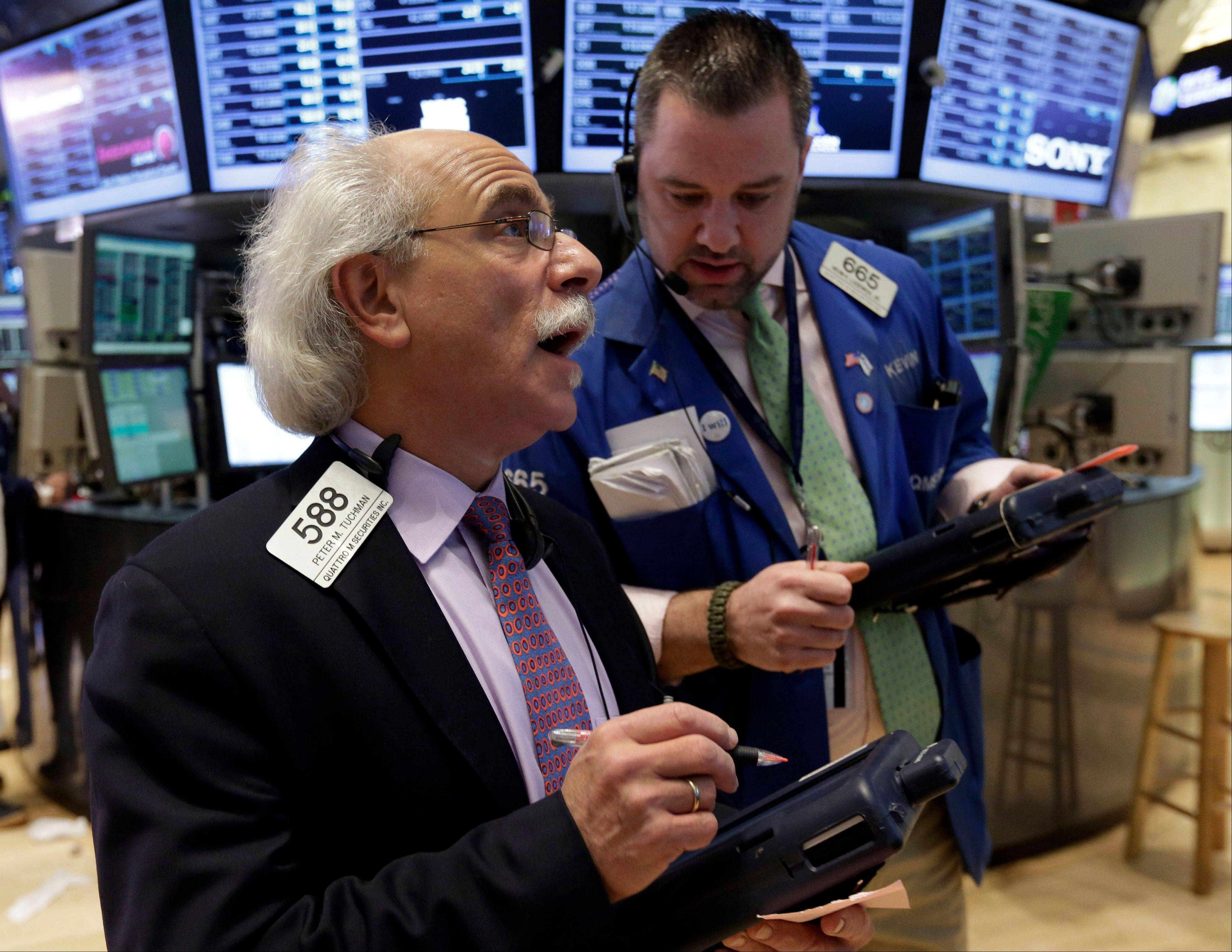 Traders Peter Tuchman, left, and Kevin Lodewick work Friday on the floor of the New York Stock Exchange.