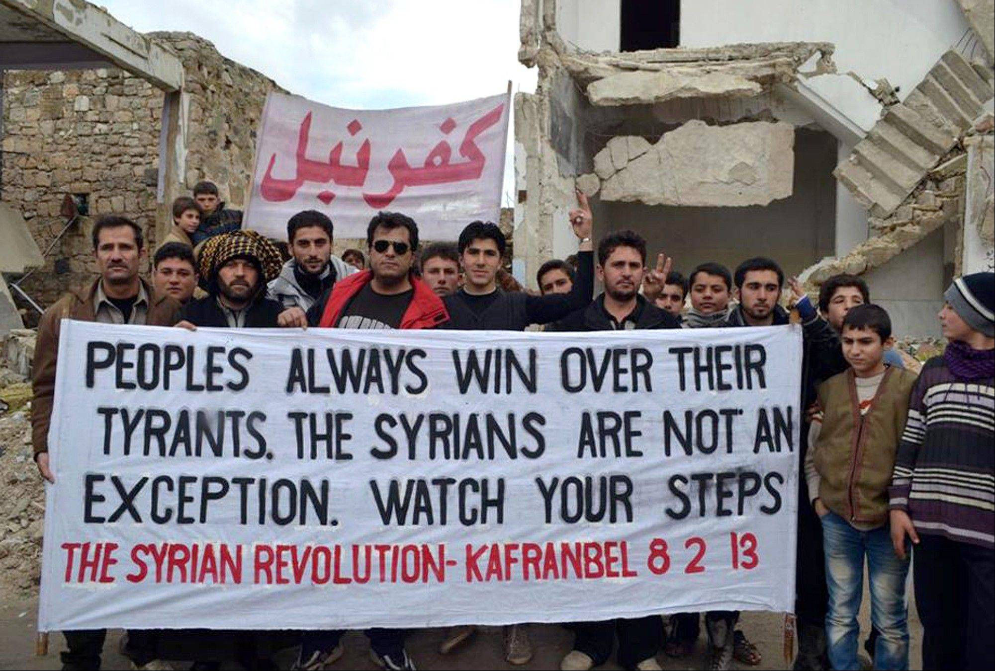Associated Press/Image provided by Edlib News Network, ENN Anti-Syrian regime protesters hold a banner Friday during a demonstration, at Kafr Nabil town, in Idlib province, northern Syria.