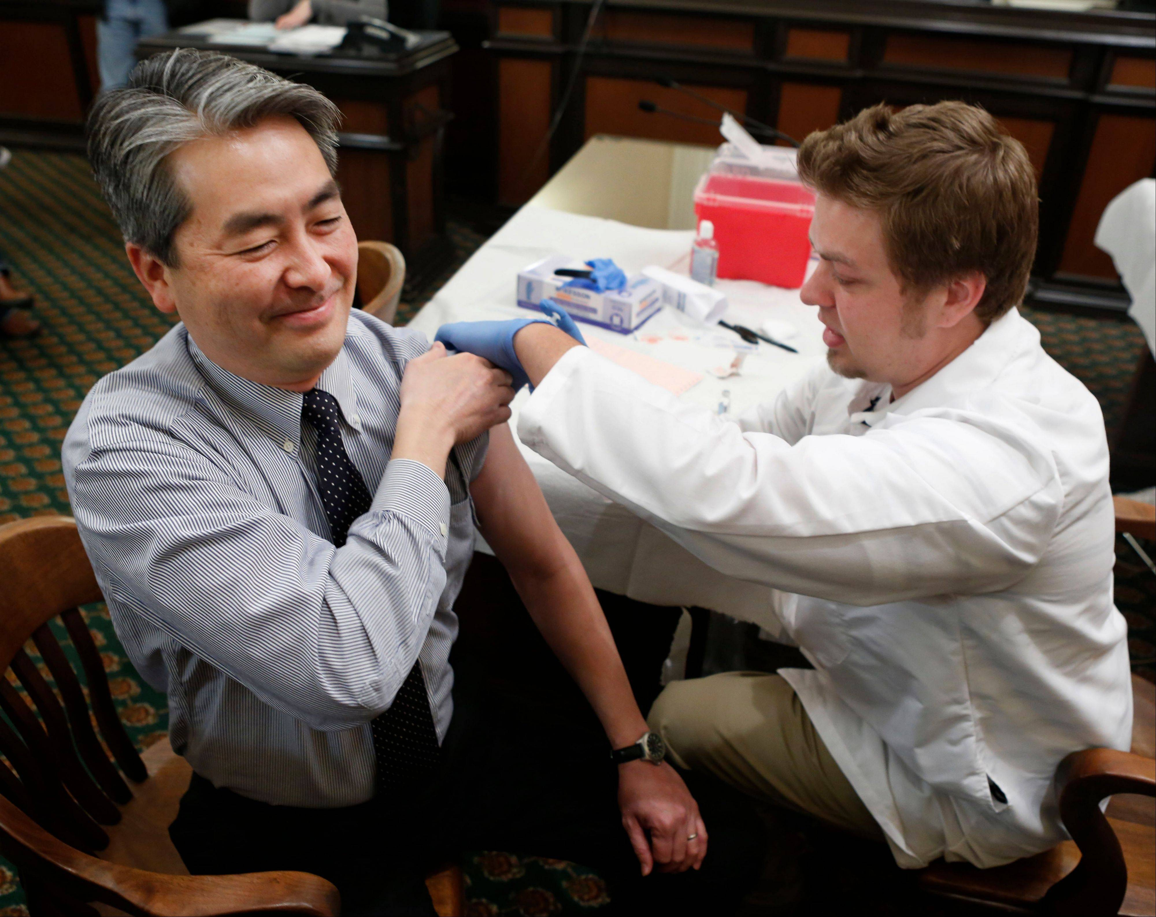 Associated Press/Monday, Jan. 28 , 2013 Torrance, Calif., assemblyman Al Muratsuchi reacts as he receives a flu shot from Tyler Poncy, a licensed vocational nurse during a free flu vaccine clinic at the Capitol in Sacramento.